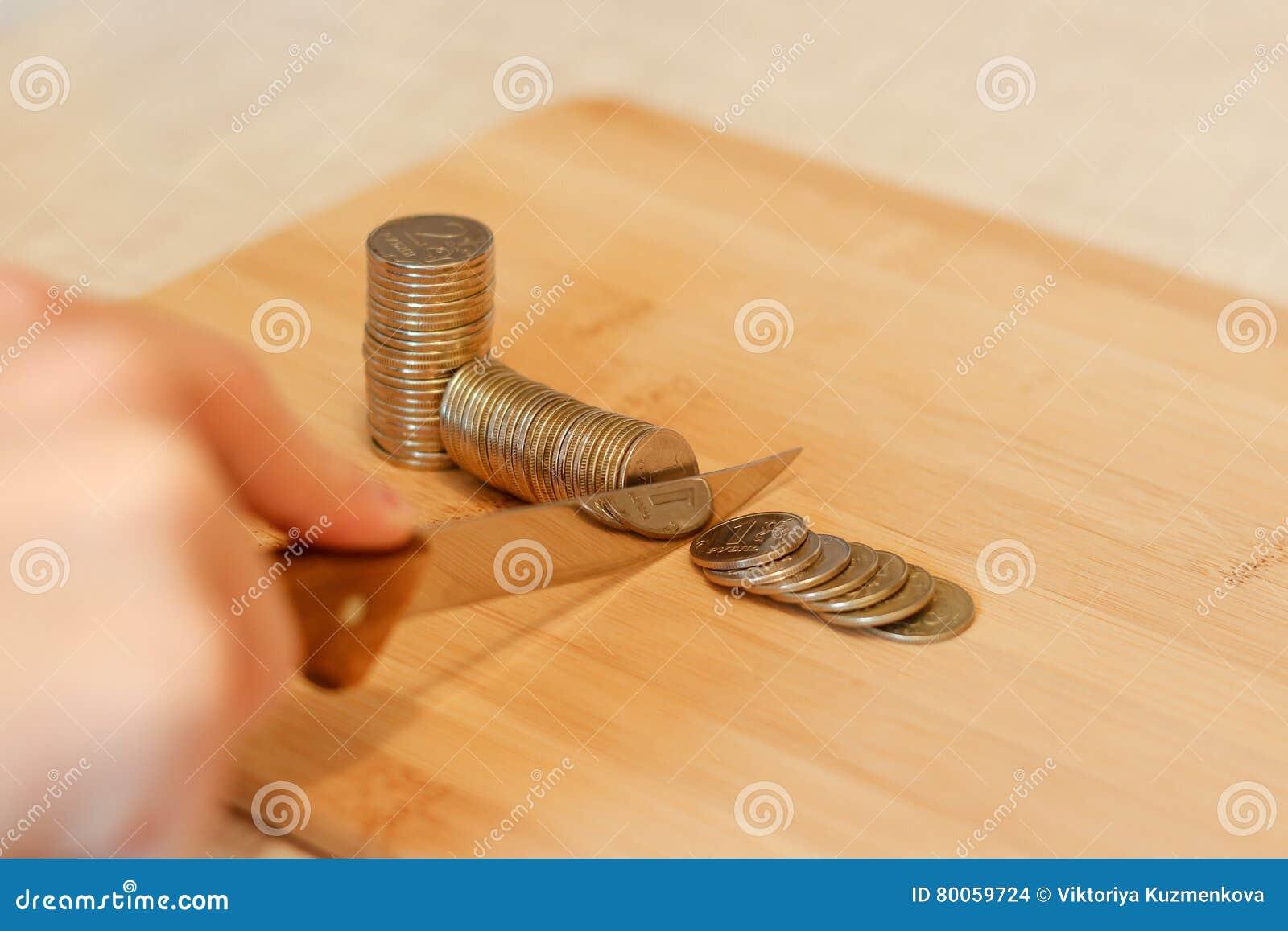 Hand met een mes die een stapel van muntstuk snijden Concept besnoeiingen op de begroting