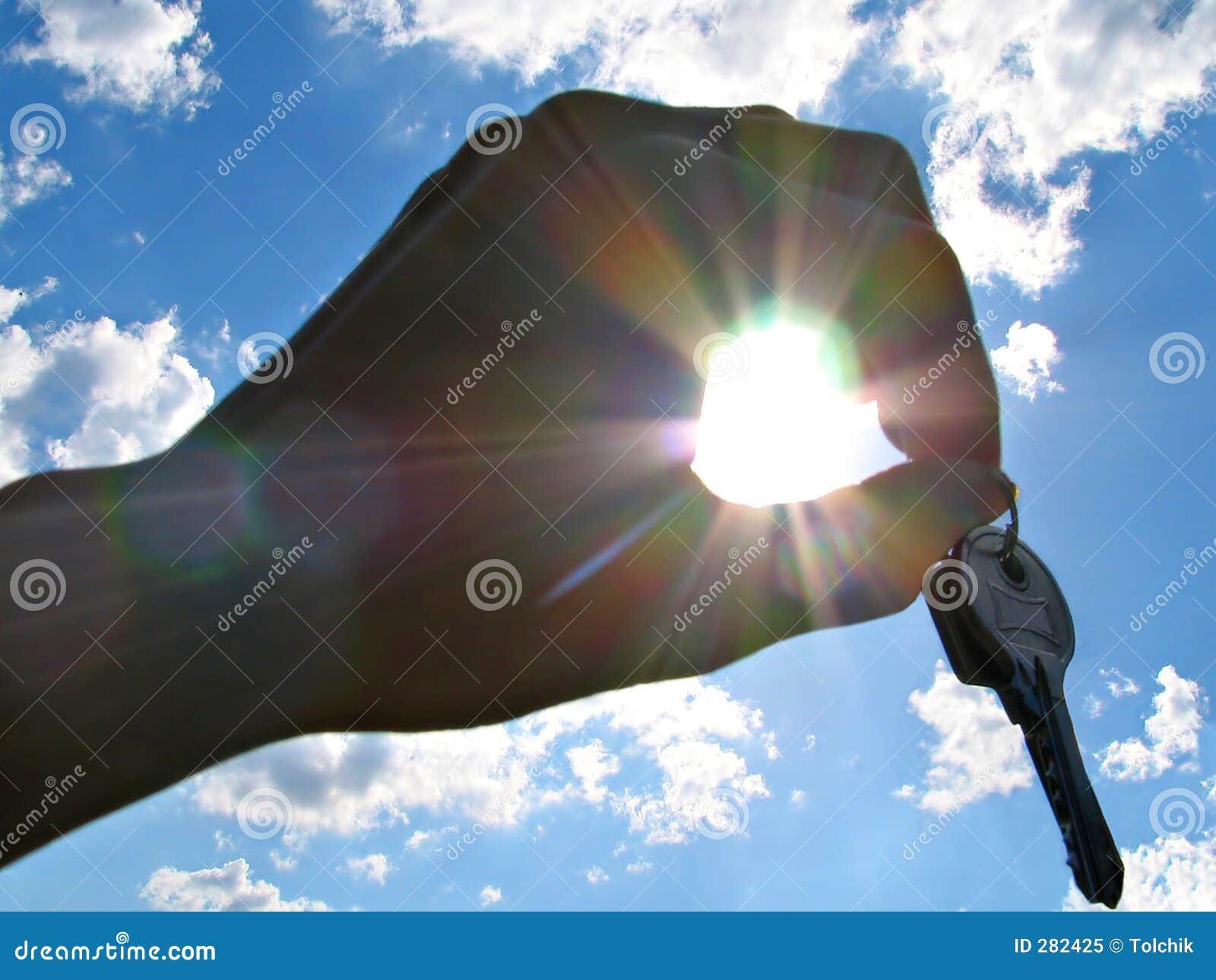 Hand met sleutels met geluk in stralen van de zon
