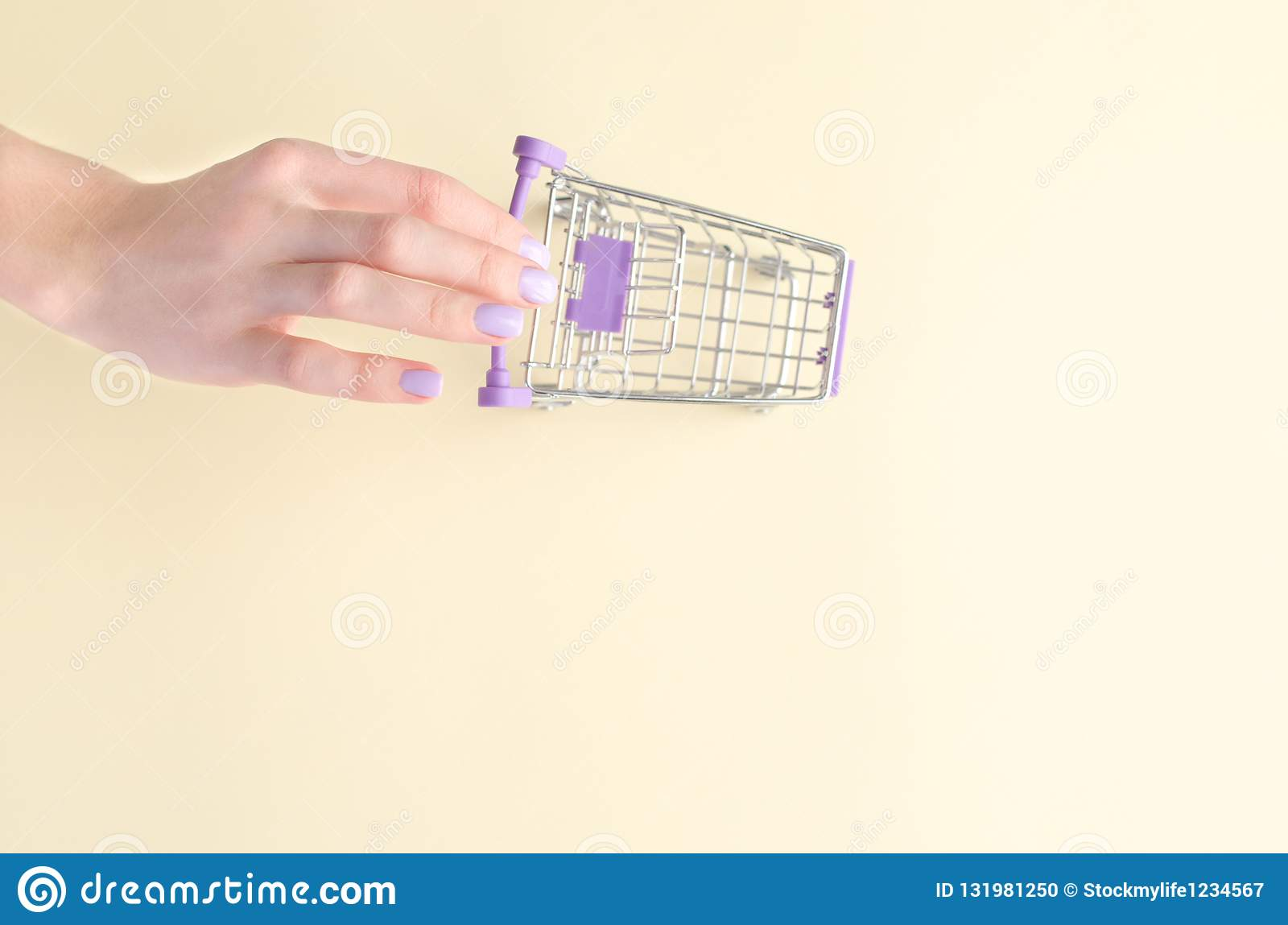 A hand with a miniature shopping trolley.