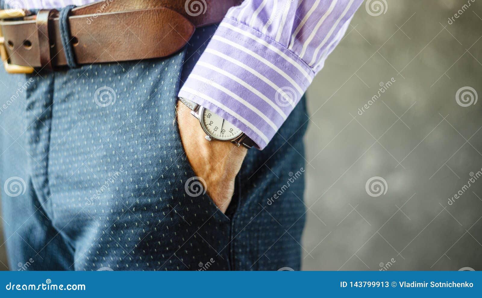 Hand mit Armbanduhr in der Tasche