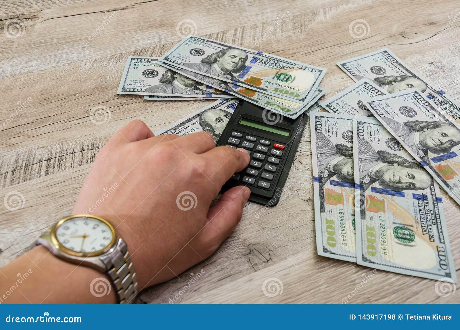 Hand mit Armbanduhr, Taschenrechner und Dollar auf einem hölzernen Hintergrund