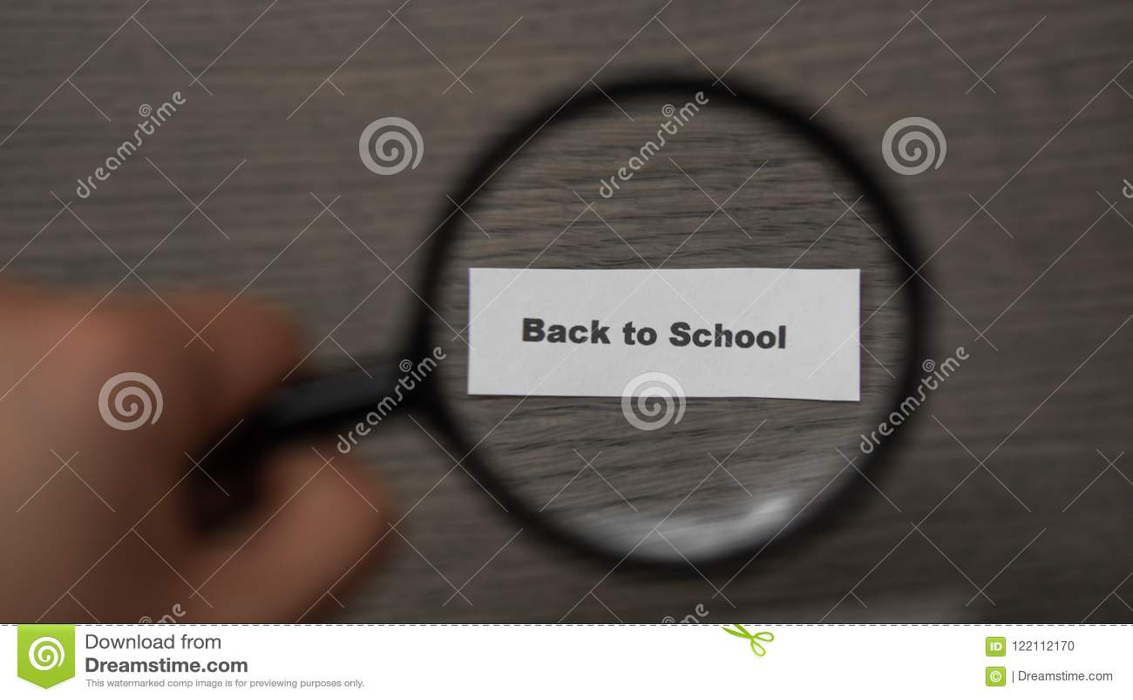 Hand mit einer Lupe auf einem hölzernen Hintergrund Vergrößerungsglas vergrößert die Phrase zurück zu Schule Konzept der Schule