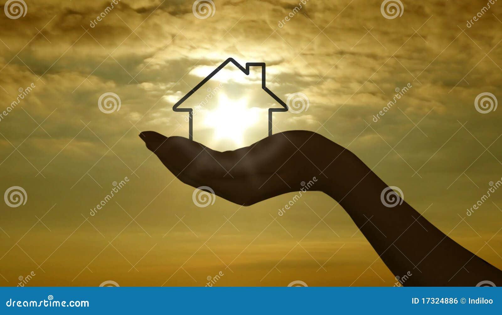 Hand mit Haus am Sonnenuntergang