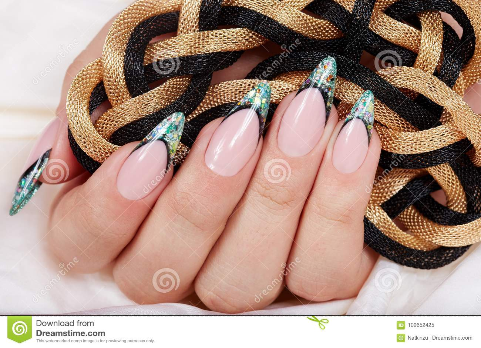 Hand mit langen künstlichen Franzosen manikürte die Nägel, die mit Funkeln verziert wurden