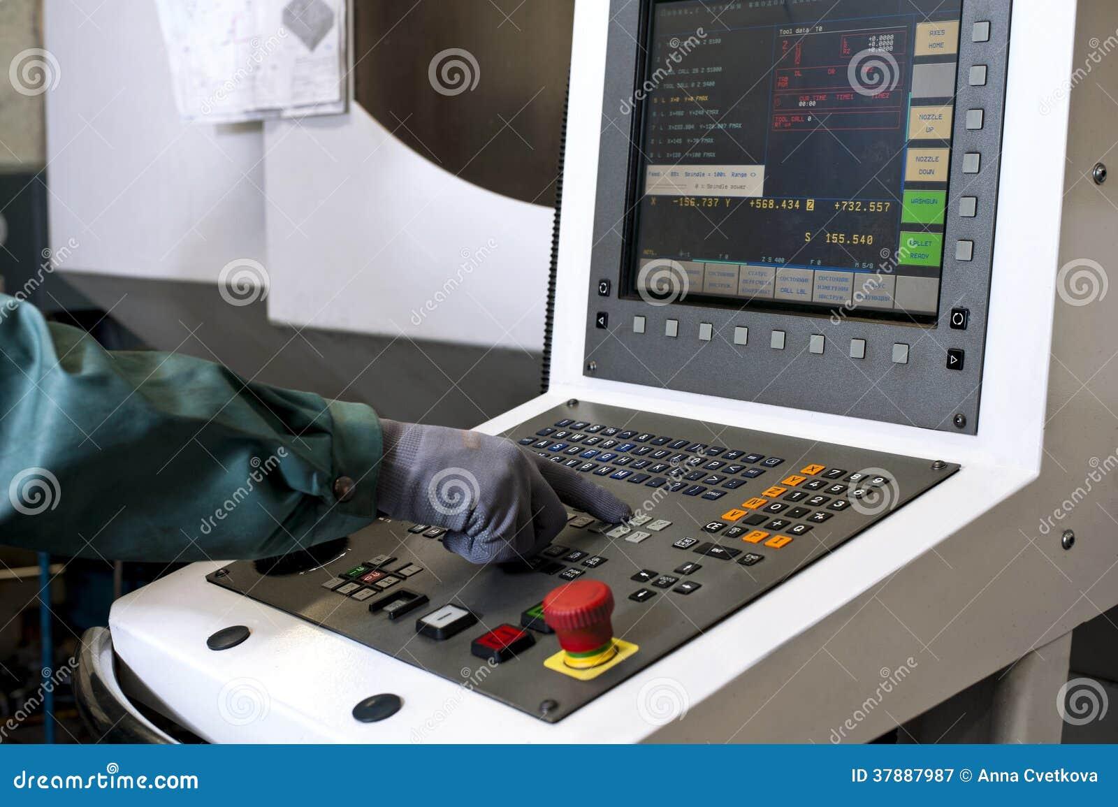 Hand op het controlebord van een cnc programmeerbare machine