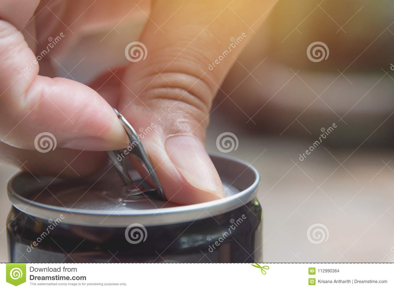Hand opening an iron can. Can with a drink of cola