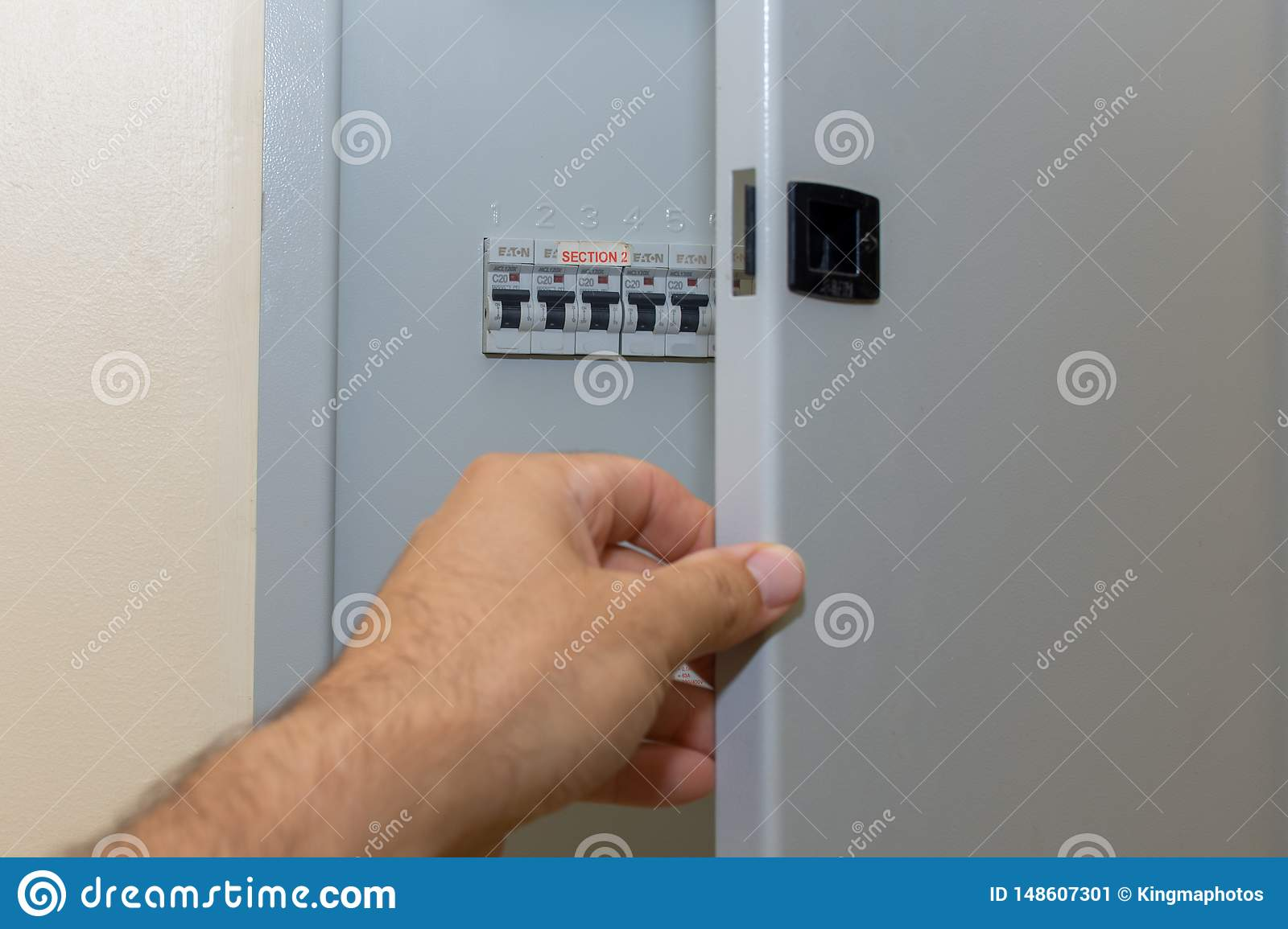 Hand opens fuse box in a residential house looking at the electrical breakers fixing loss of power