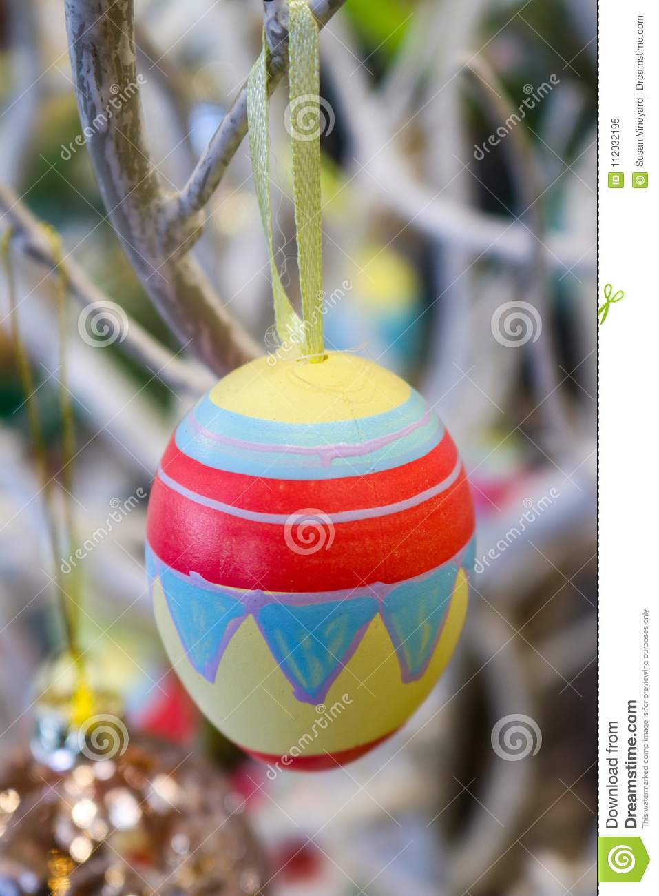 Hand painted easter egg hanging on a white tree with bokeh background
