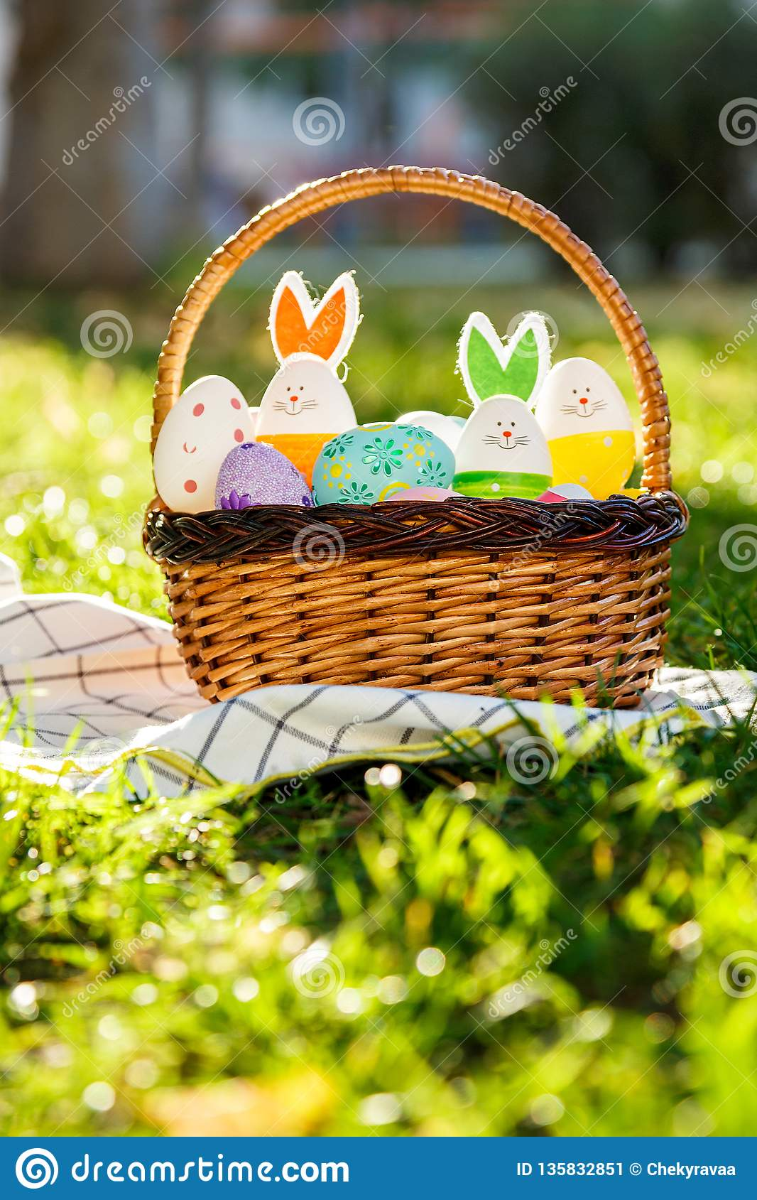 Hand painted Easter eggs and bunny in big rattan basket on green grass on white towel. Traditional decoration for Easter