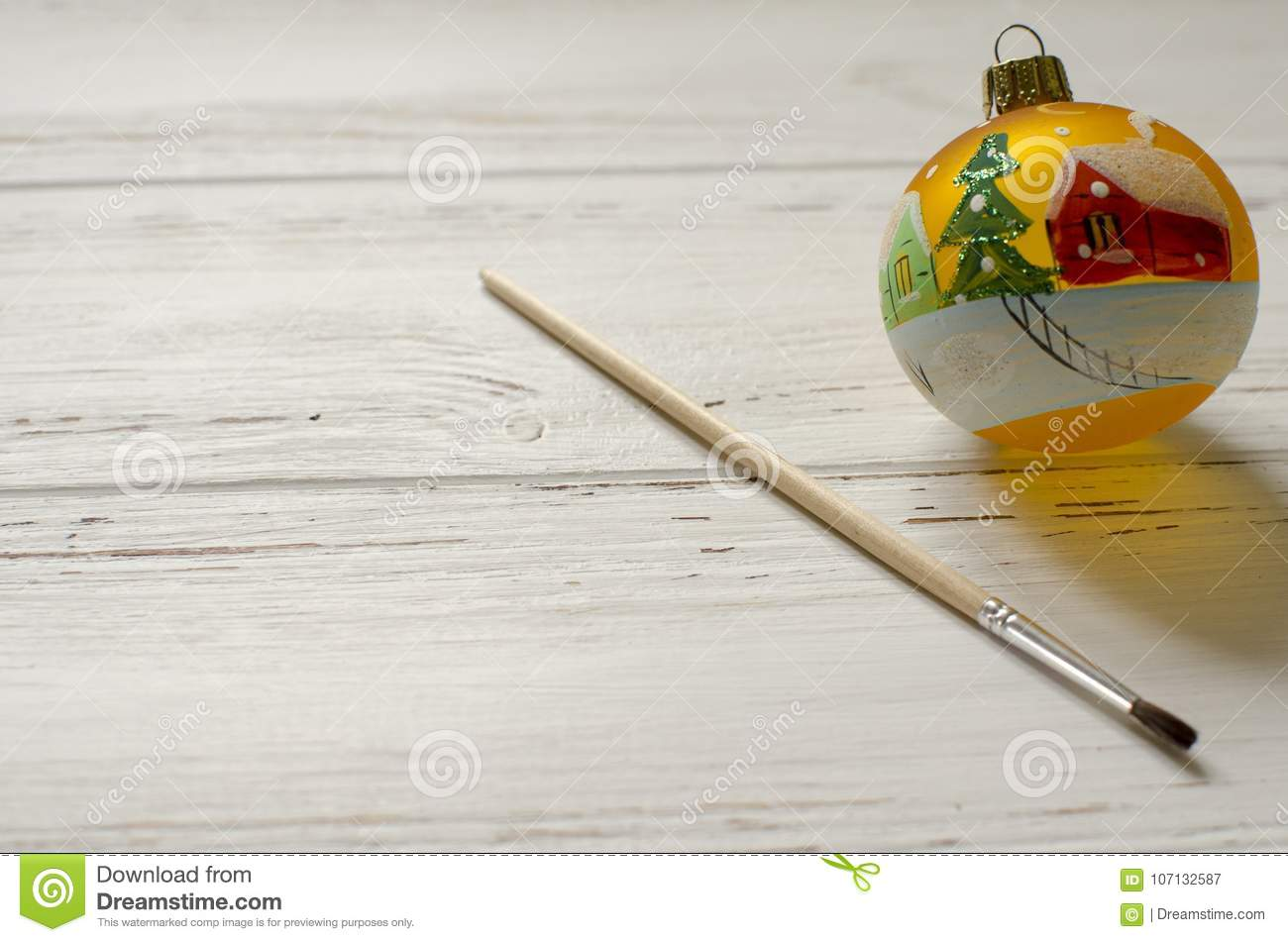 Hand-painted new year ball with brush on white wooden background