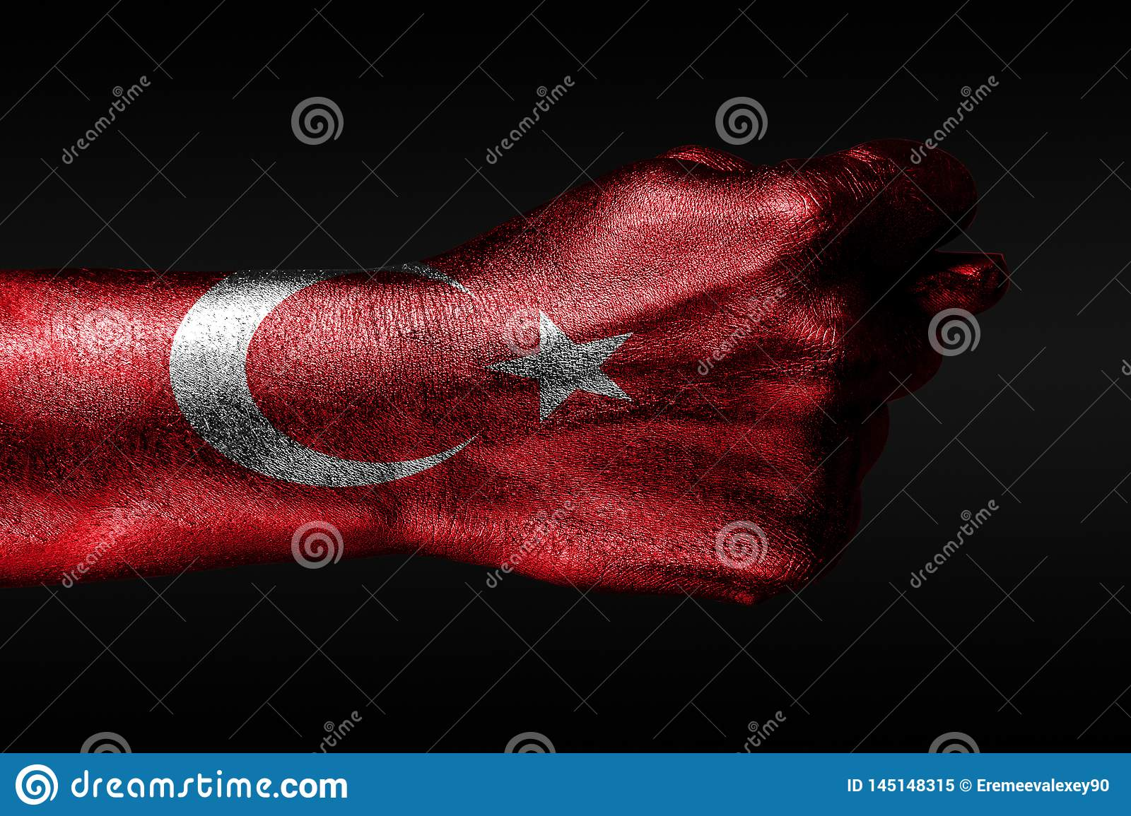 A hand with a painted Turkey flag shows a fig, a sign of aggression, disagreement, a dispute on a dark background
