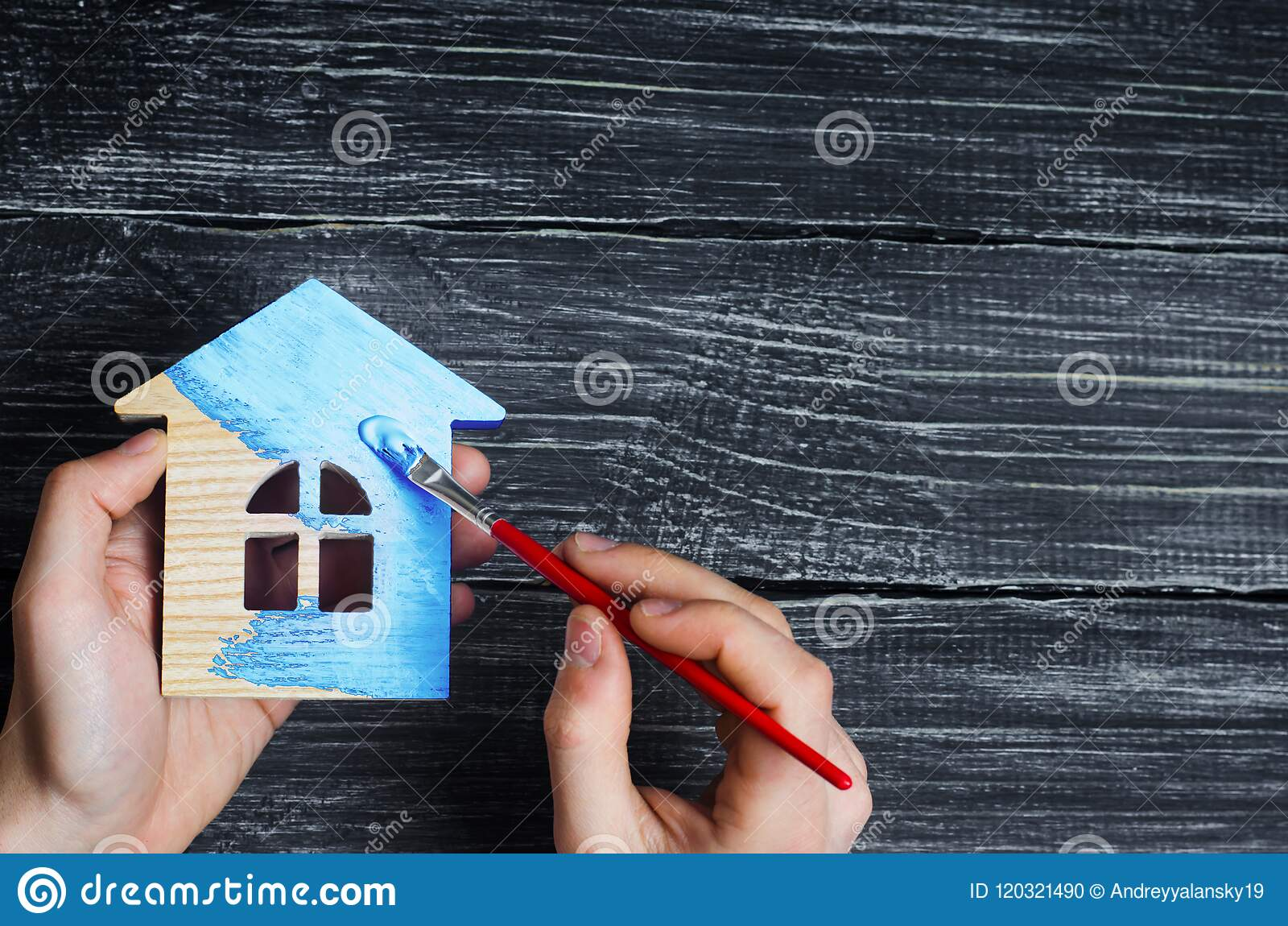 Hand paints a house in to blue color. Concept of repair, hobby, work. Repair and painting of wooden house figurines. Toy house