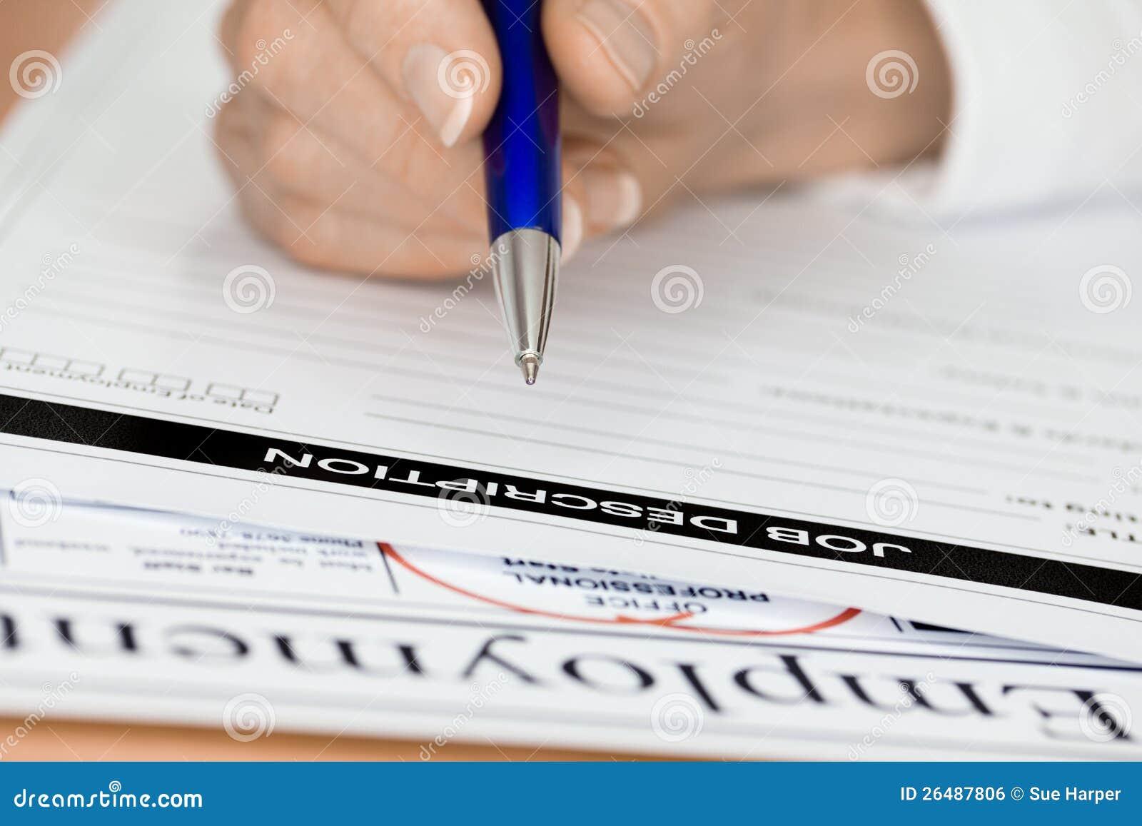 hand with pen writing employee job description stock photo image