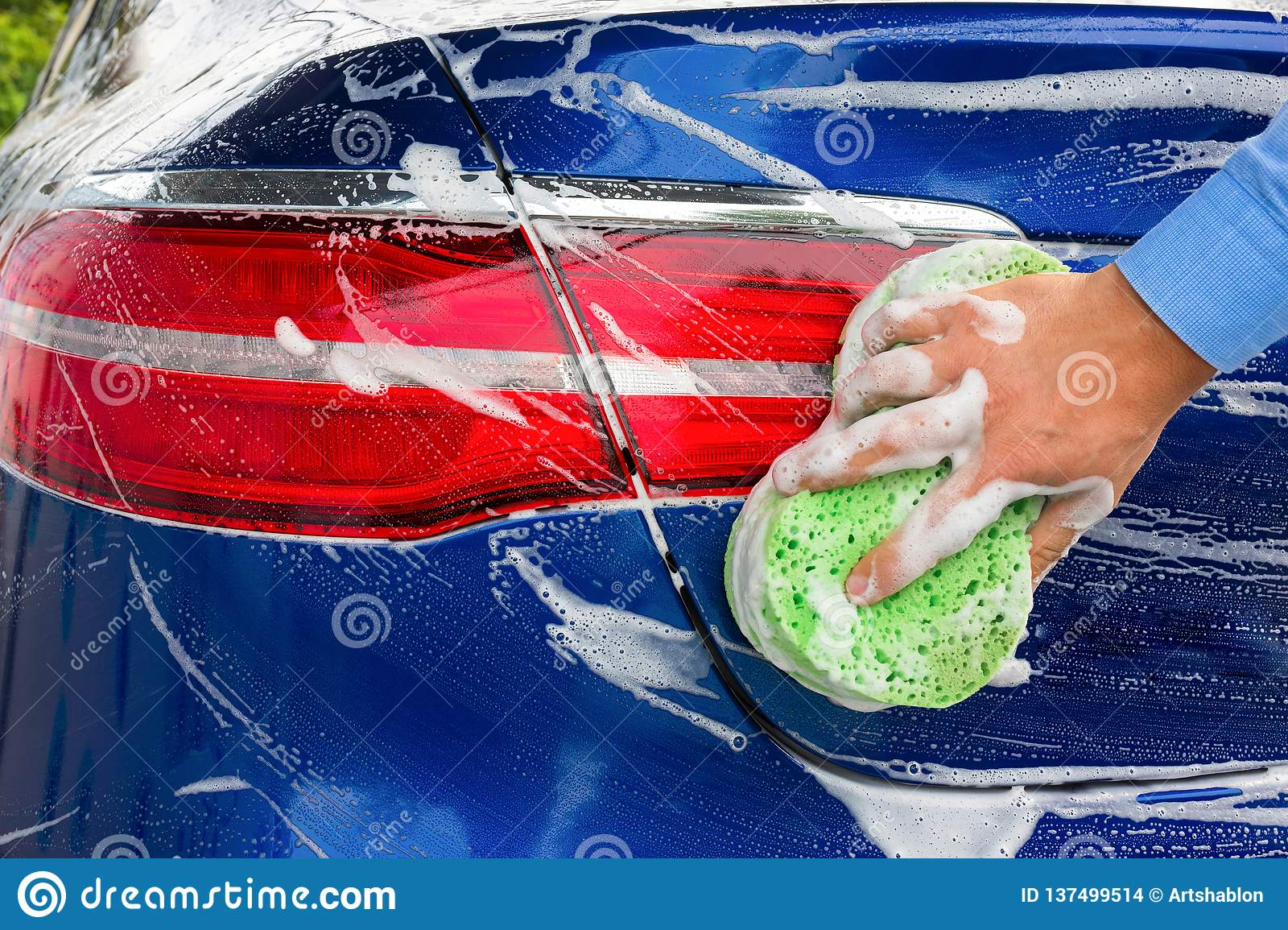 Hand of the person with a sponge, the washing blue car. Close-up