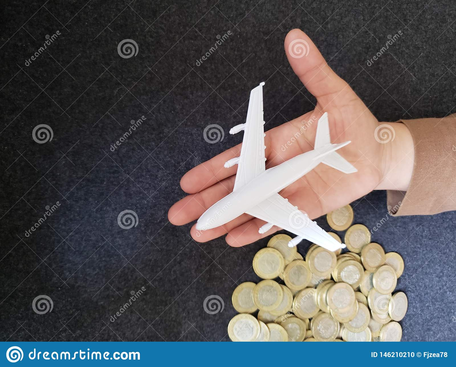 hand of a person with a white airplane figure and savings in mexican pesos