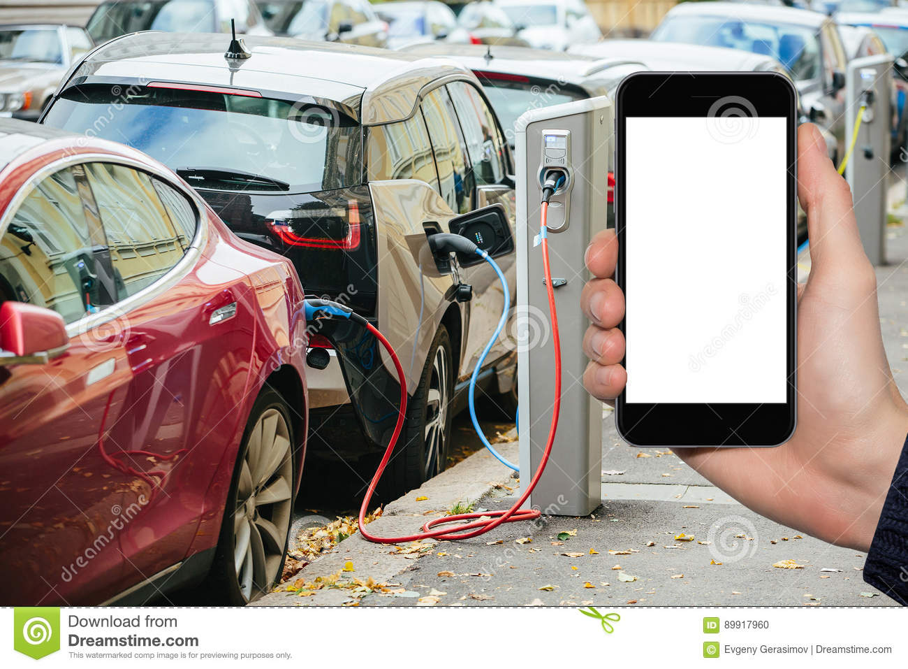 Hand With Phone On A Background Of Electric Cars Charging Points
