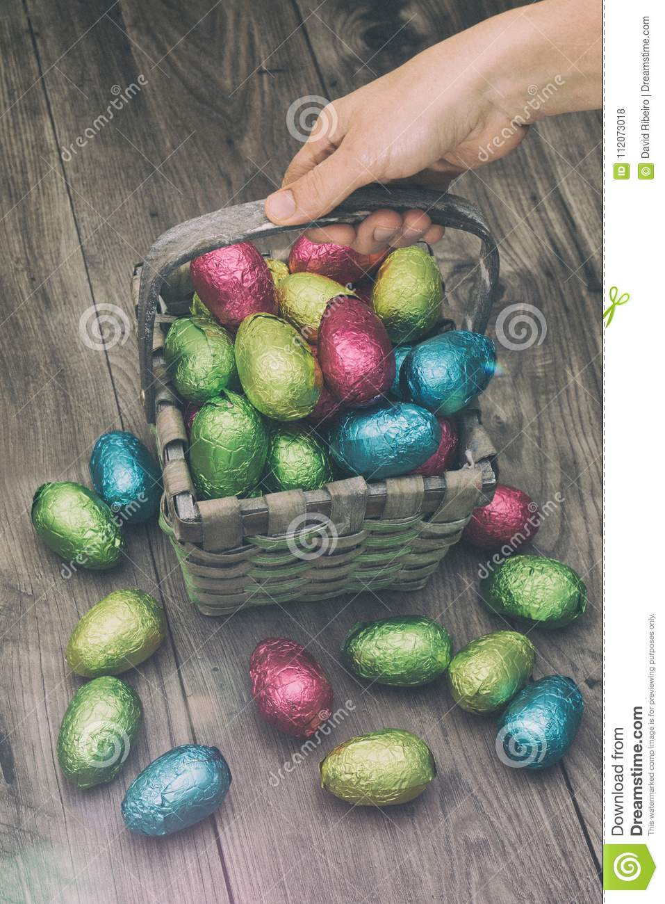 Hand picking up a straw basket filled with Easter chocolate eggs wrapped in colorful tinfoil