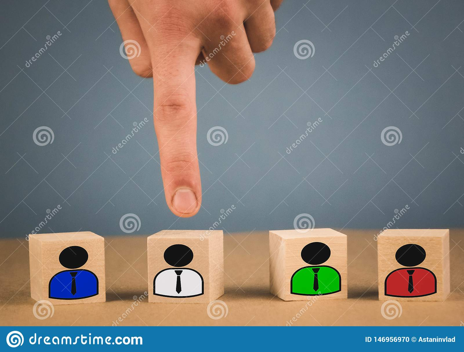 hand picks a wooden cube with a man in a white shirt