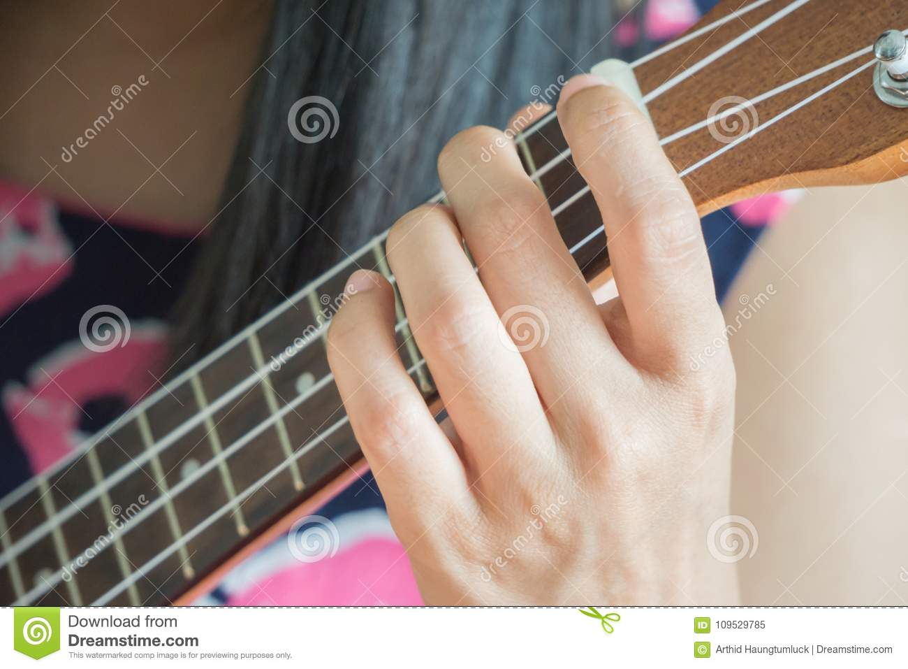 Hand playing guitar or Ukulele chord.
