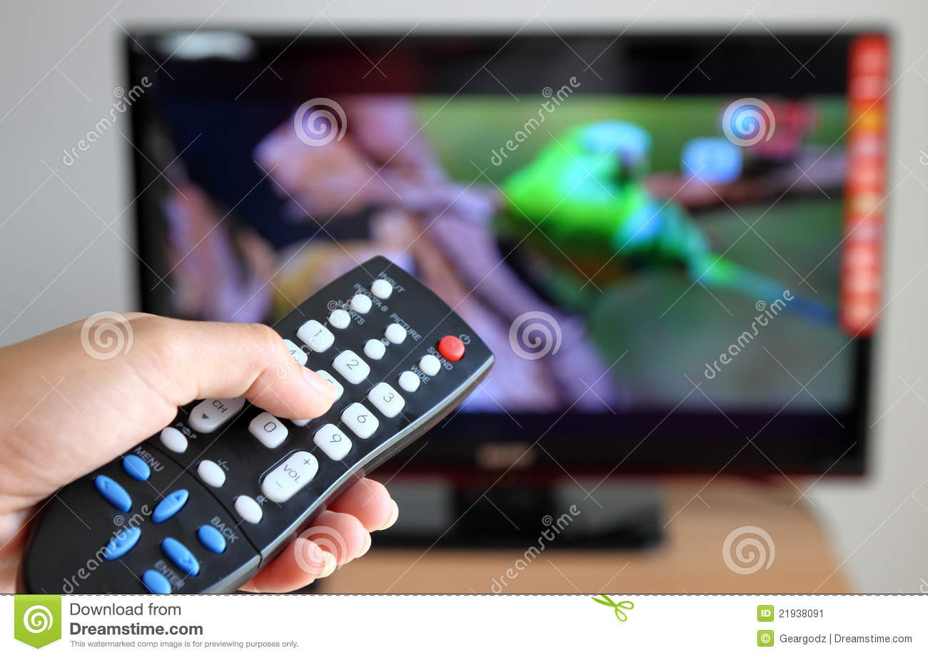 Hand pointing a tv remote control towards the tele