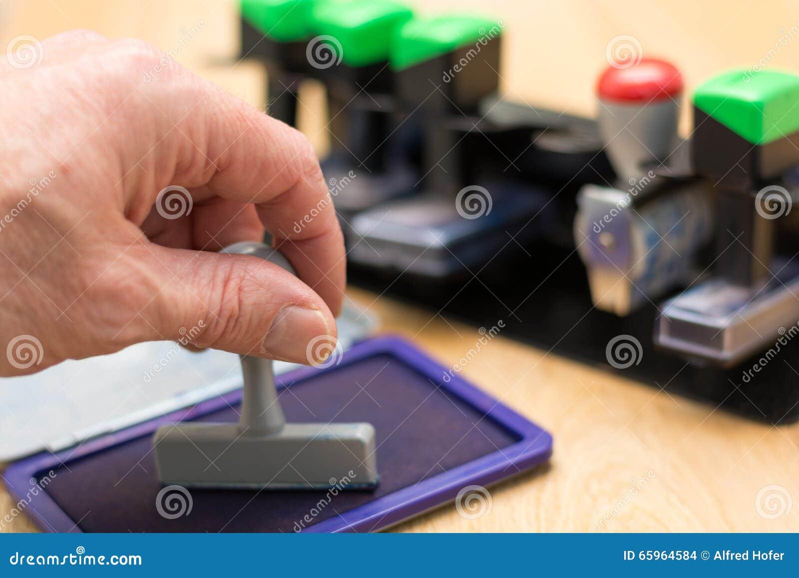 Hand presses stamp in stamp pad - Closeup