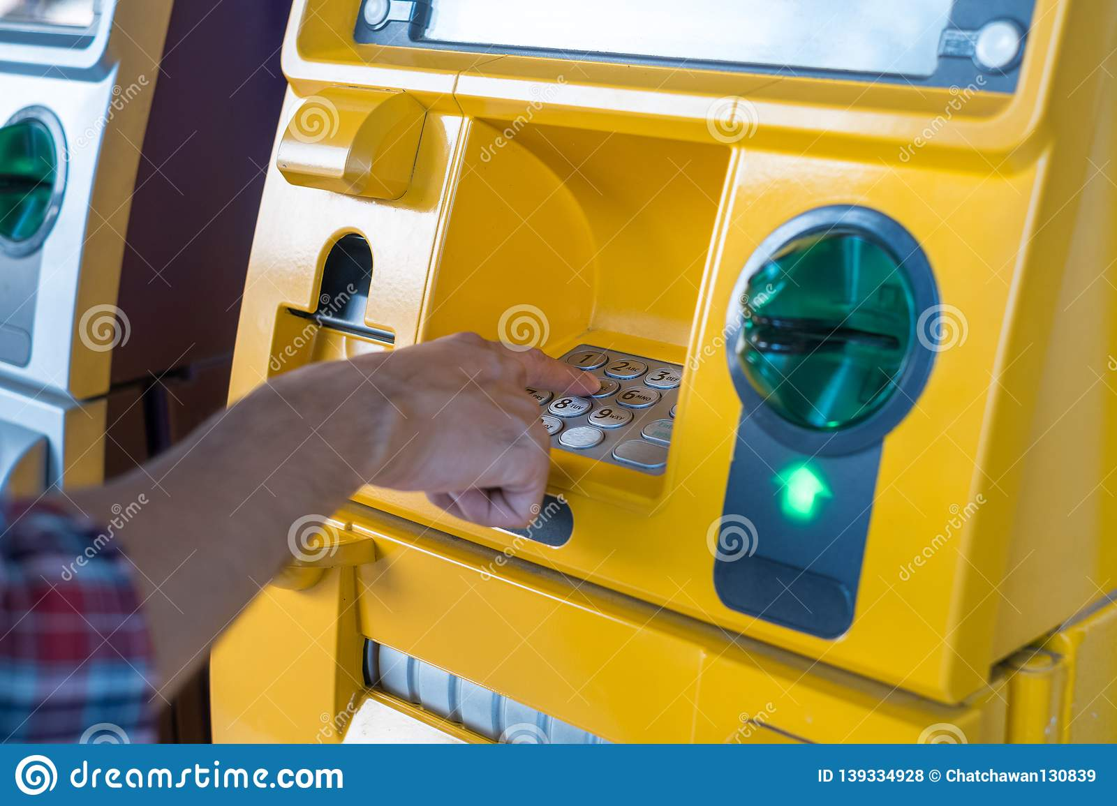 Hand pressing the code from the ATM focuses on the numbers and the finger area