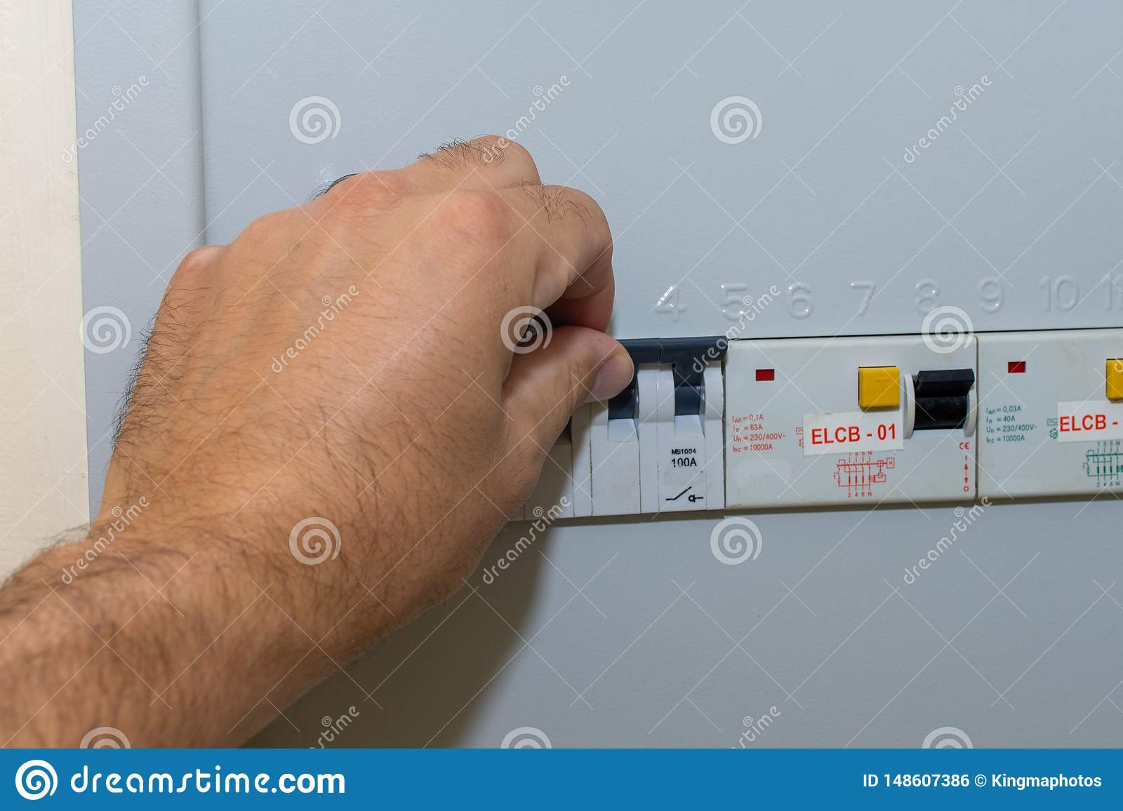 Hand pushes breaker in a fuse box in a residential house looking at the electrical breakers fixing loss of power