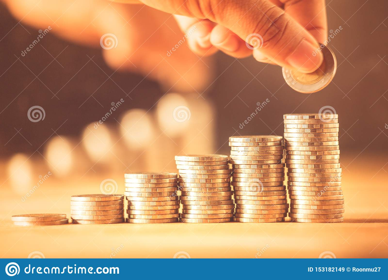 Hand putting money coins stack for save money concept. Money management is growing a business