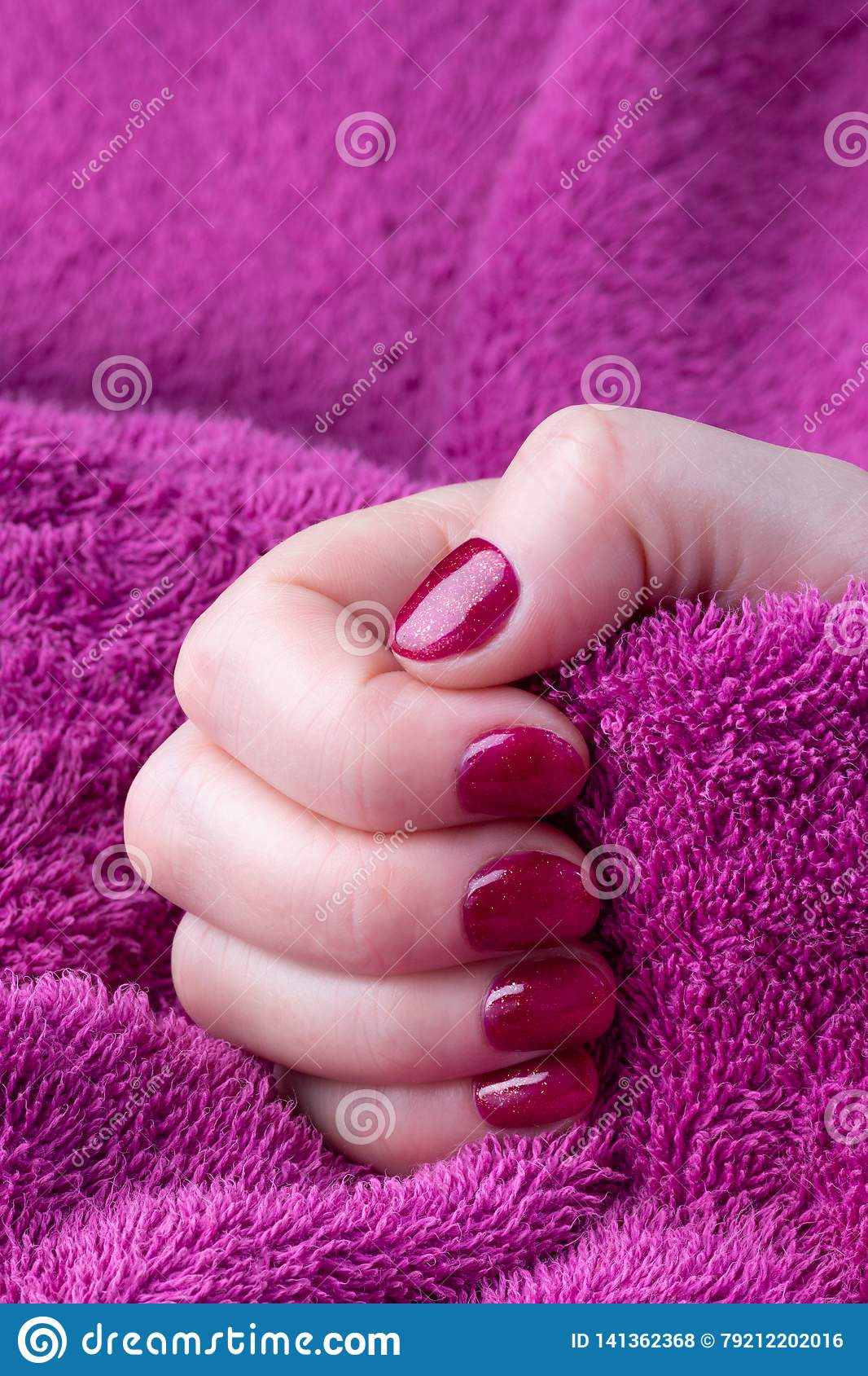 Hand with red short manicured nails with a purple towel background