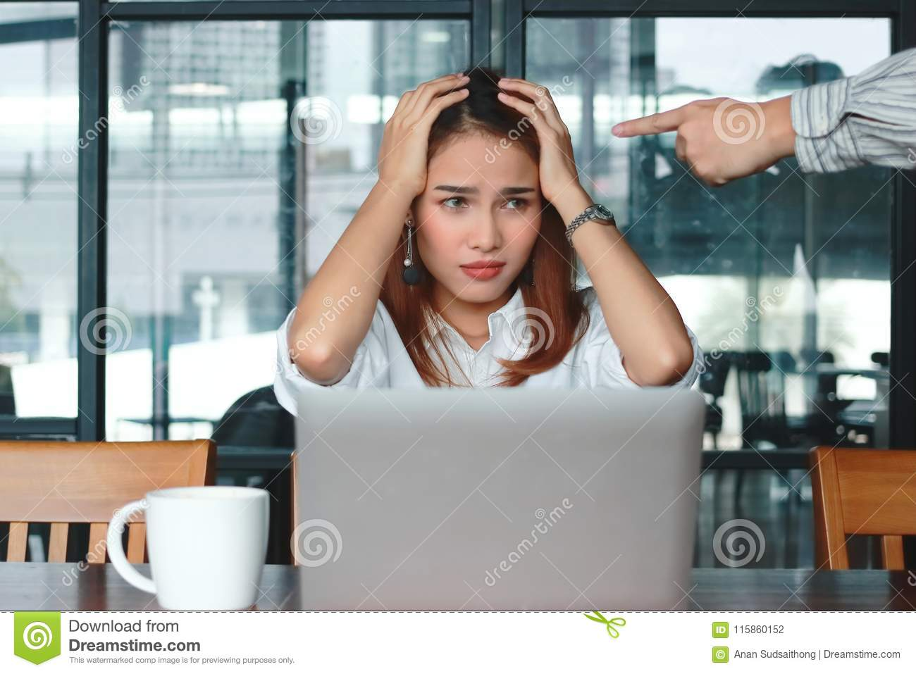 Hand`s boss pointing anxious depressed Asian business woman in office.