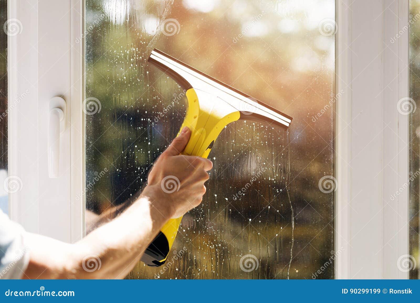 Hand schoonmakend venster met stofzuiger