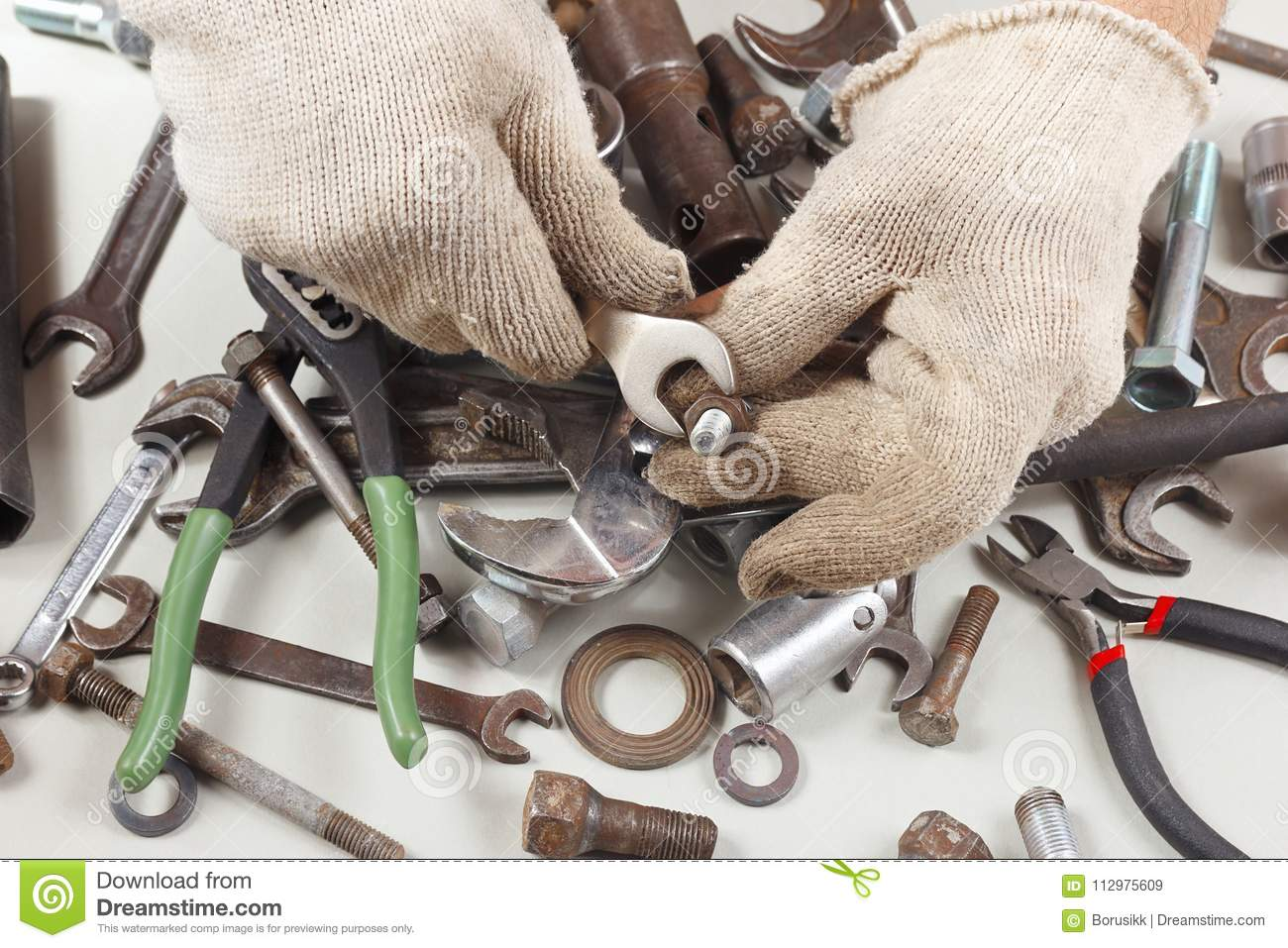 Hand of serviceman in gloves with wrench to tighten the nut
