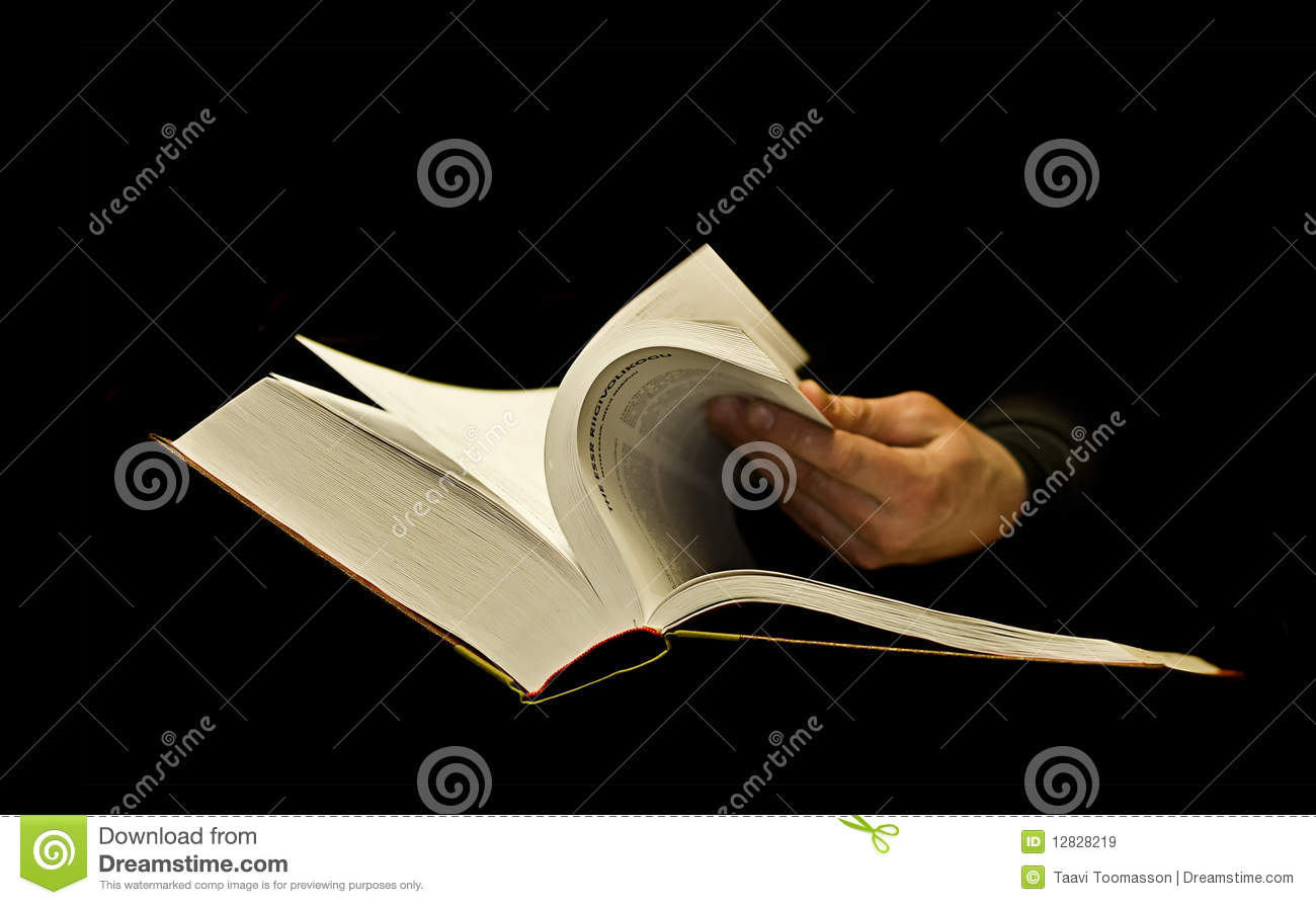 hand skimming thick book on black stock image image
