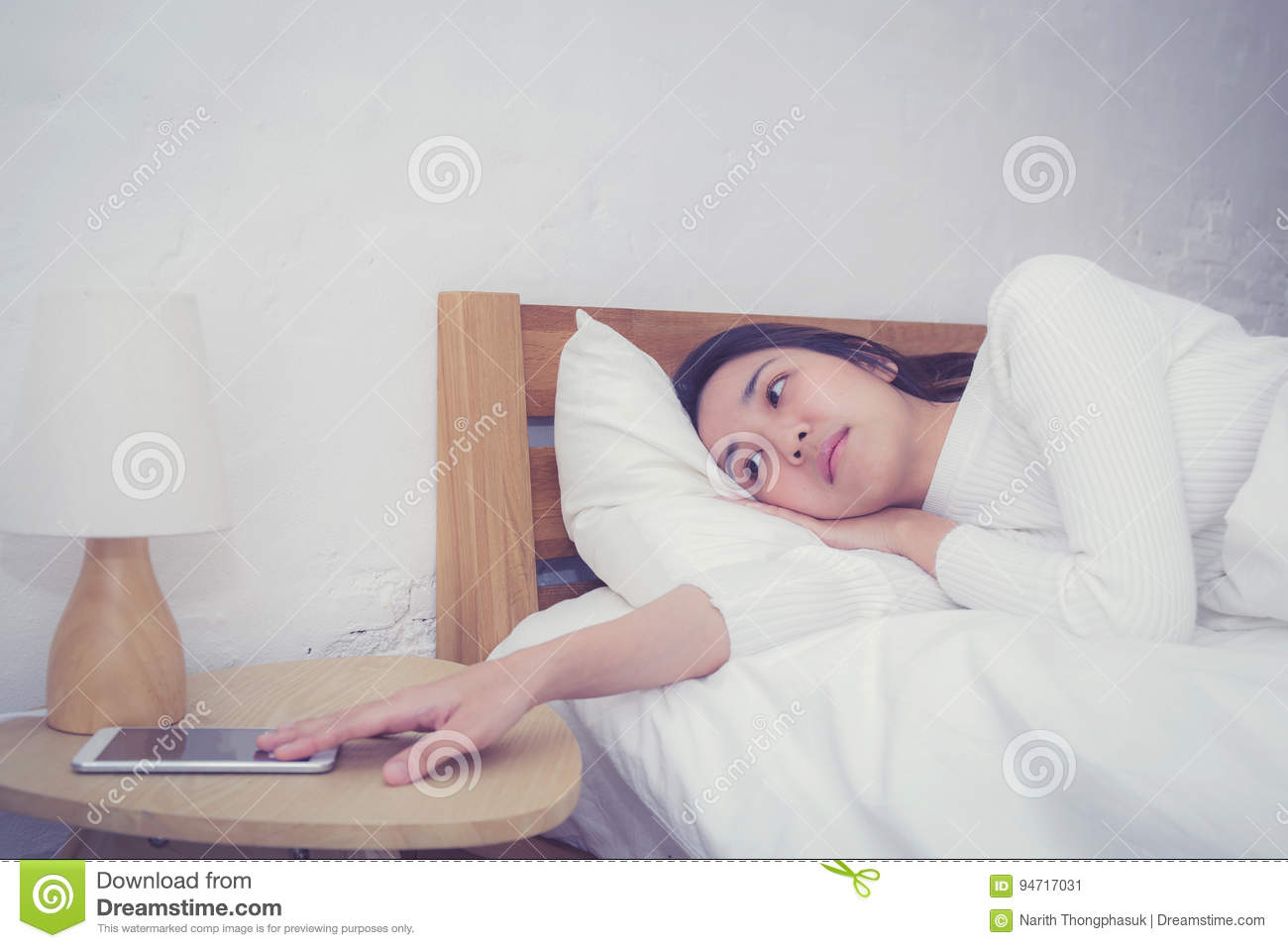 Hand of sleepy woman waking up with alarm clock on mobile phone.
