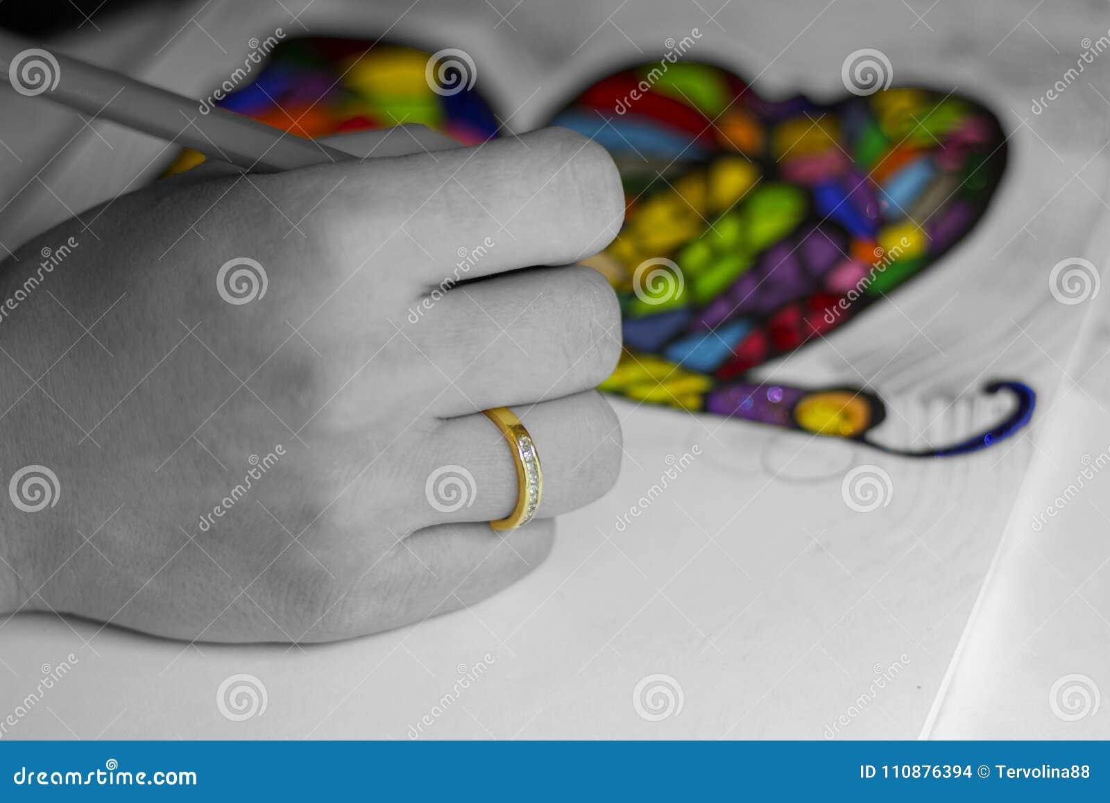 Hand som drar en färgrik regnbågefjäril