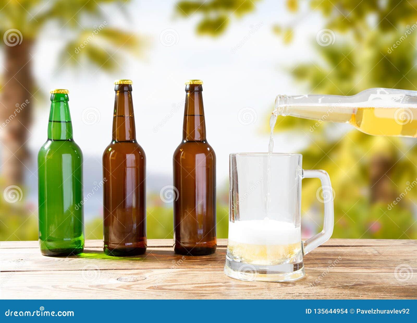 Hand som häller ljust öl i en kopp, flaskor på trätabellen