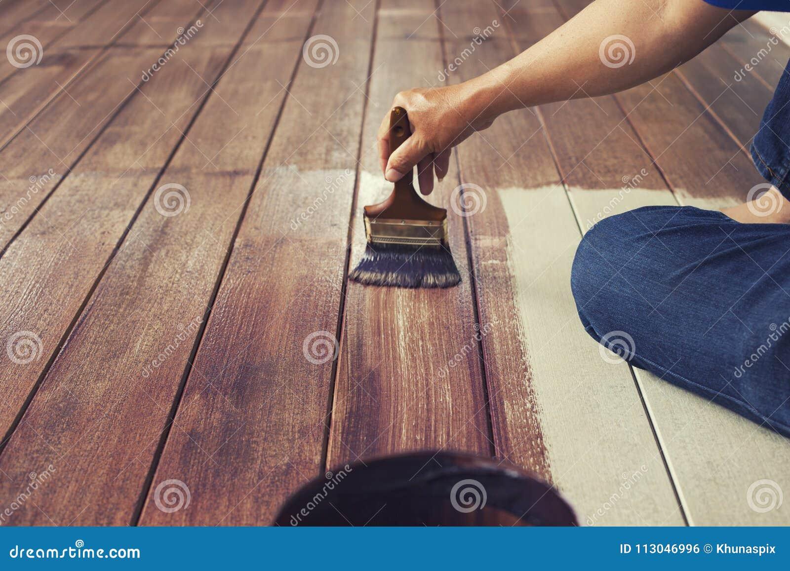 Hand som målar olje- färg på det wood golvet, diy hem- arbetsbegrepp