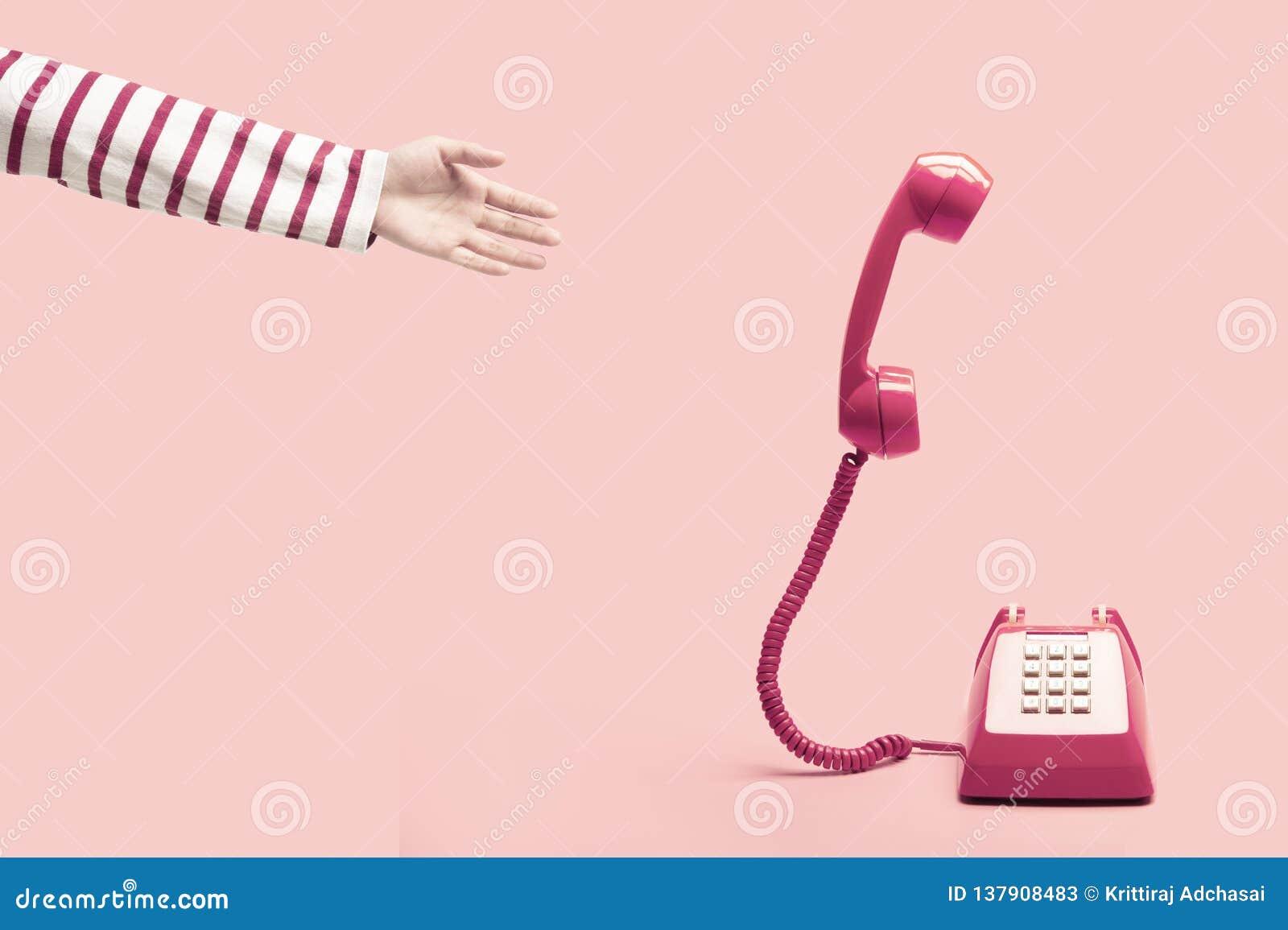 Hand som når till den rosa retro telefonen
