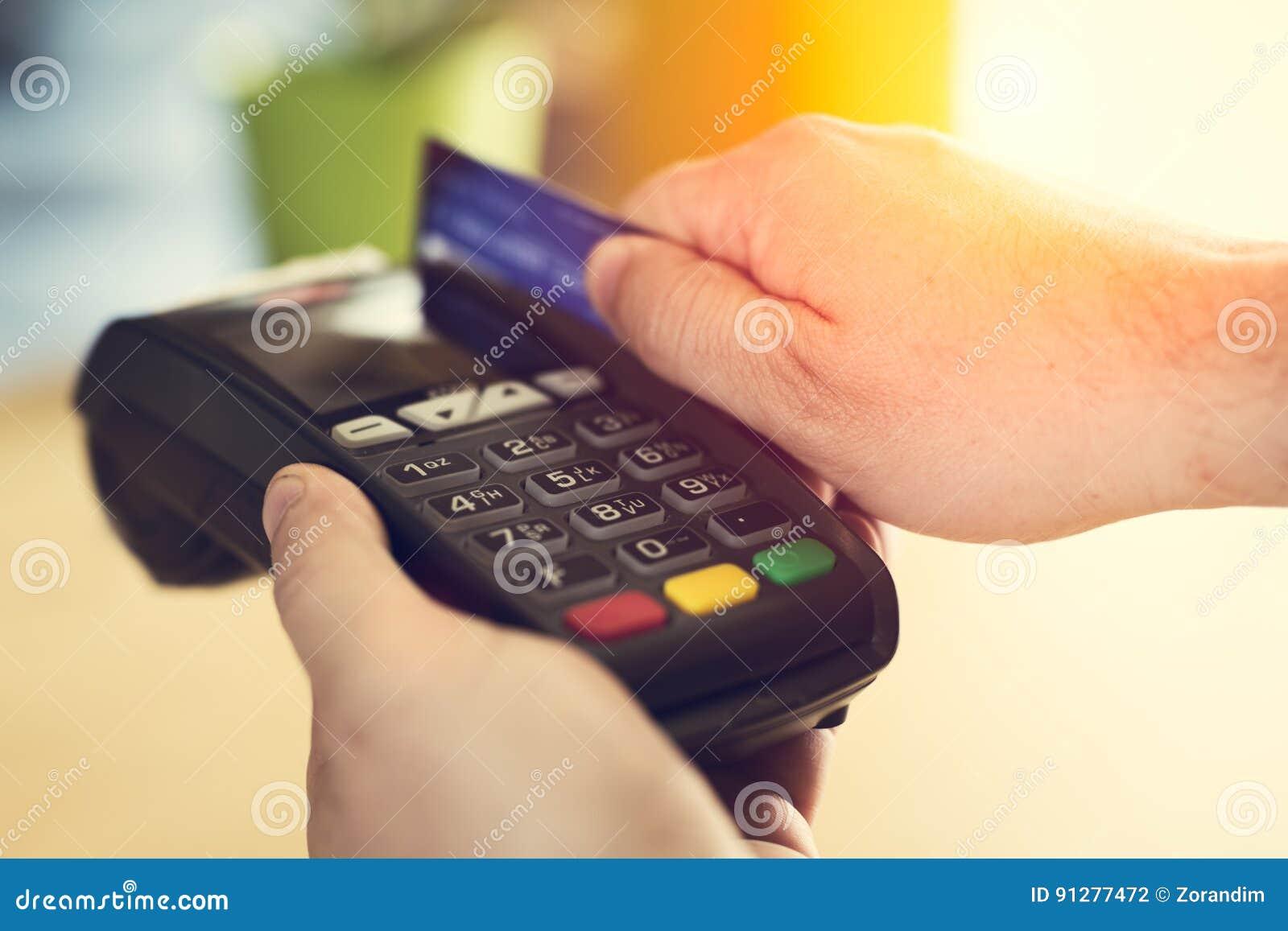 Hand som nallar kreditkorten i lager