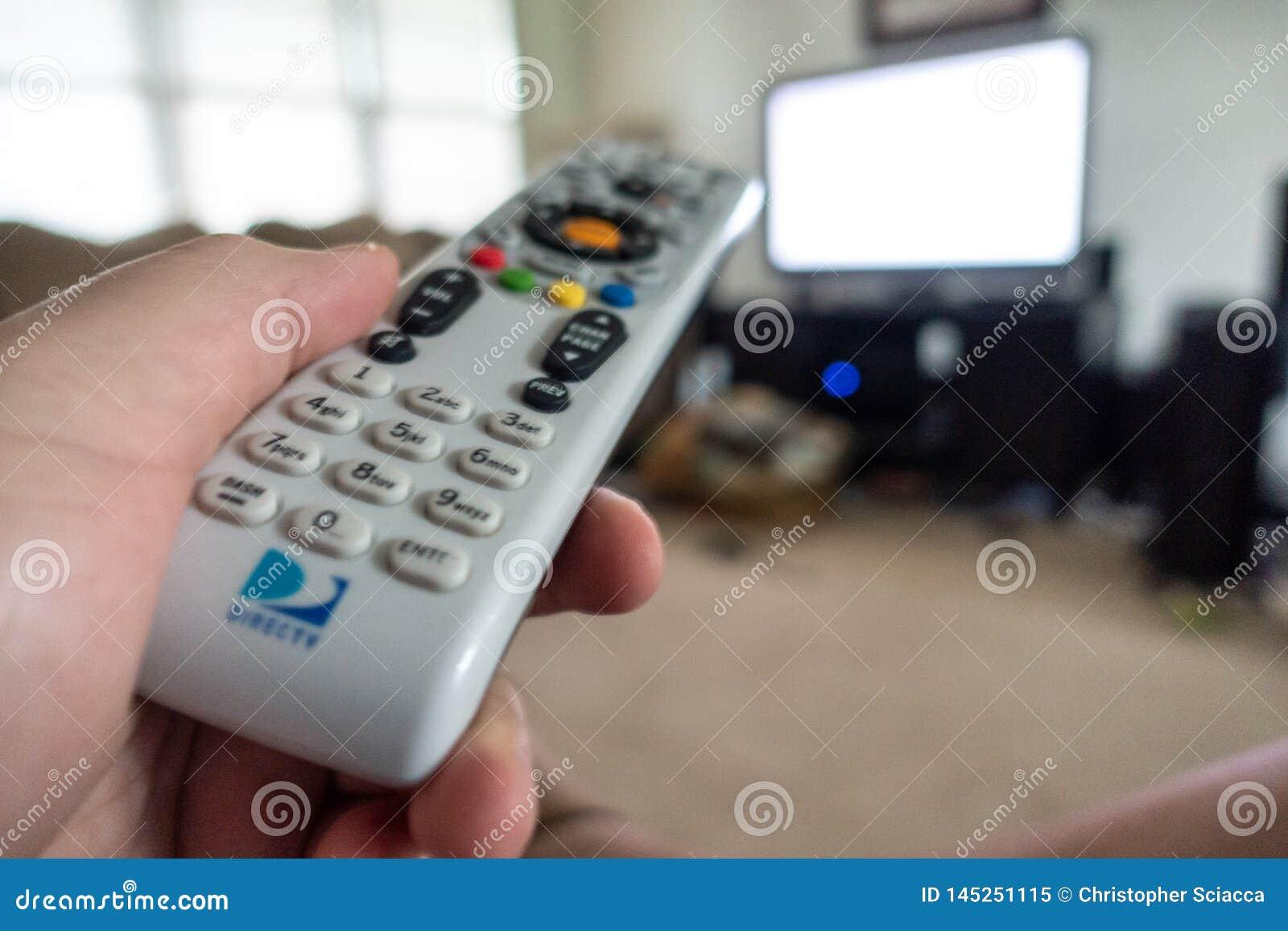 Hand som rymmer den DirecTv fjärrkontrollen som pekar på TV