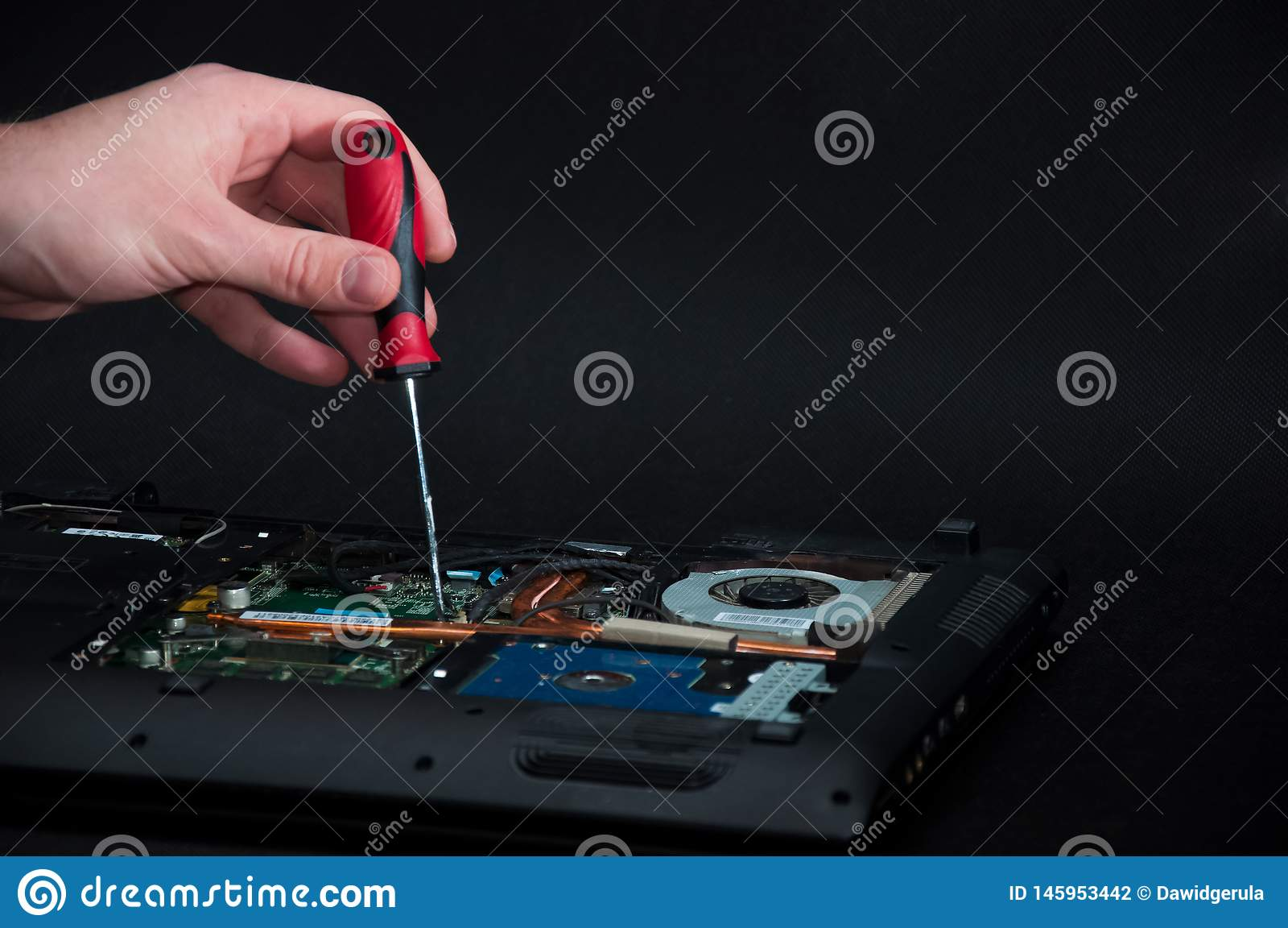 Hand som rymmer en skruvmejsel som reparerar en öppnad bärbar dator på mörk bakgrund