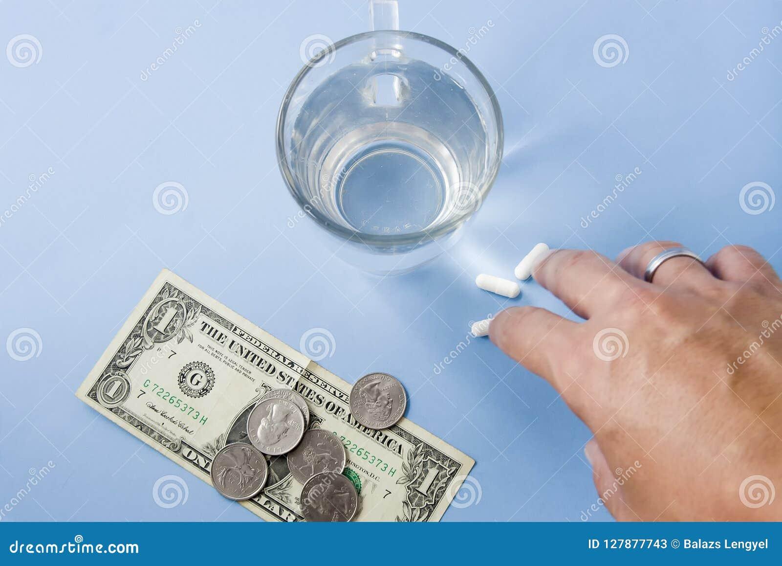Hand som tar preventivpillerar Pengar och mynt med piller och ett exponeringsglas av fre