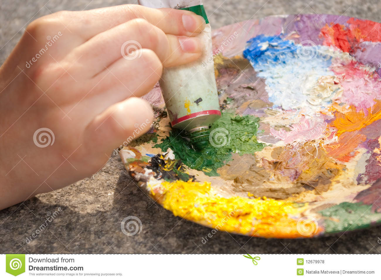 Hand squeezing green oilpaint on palette