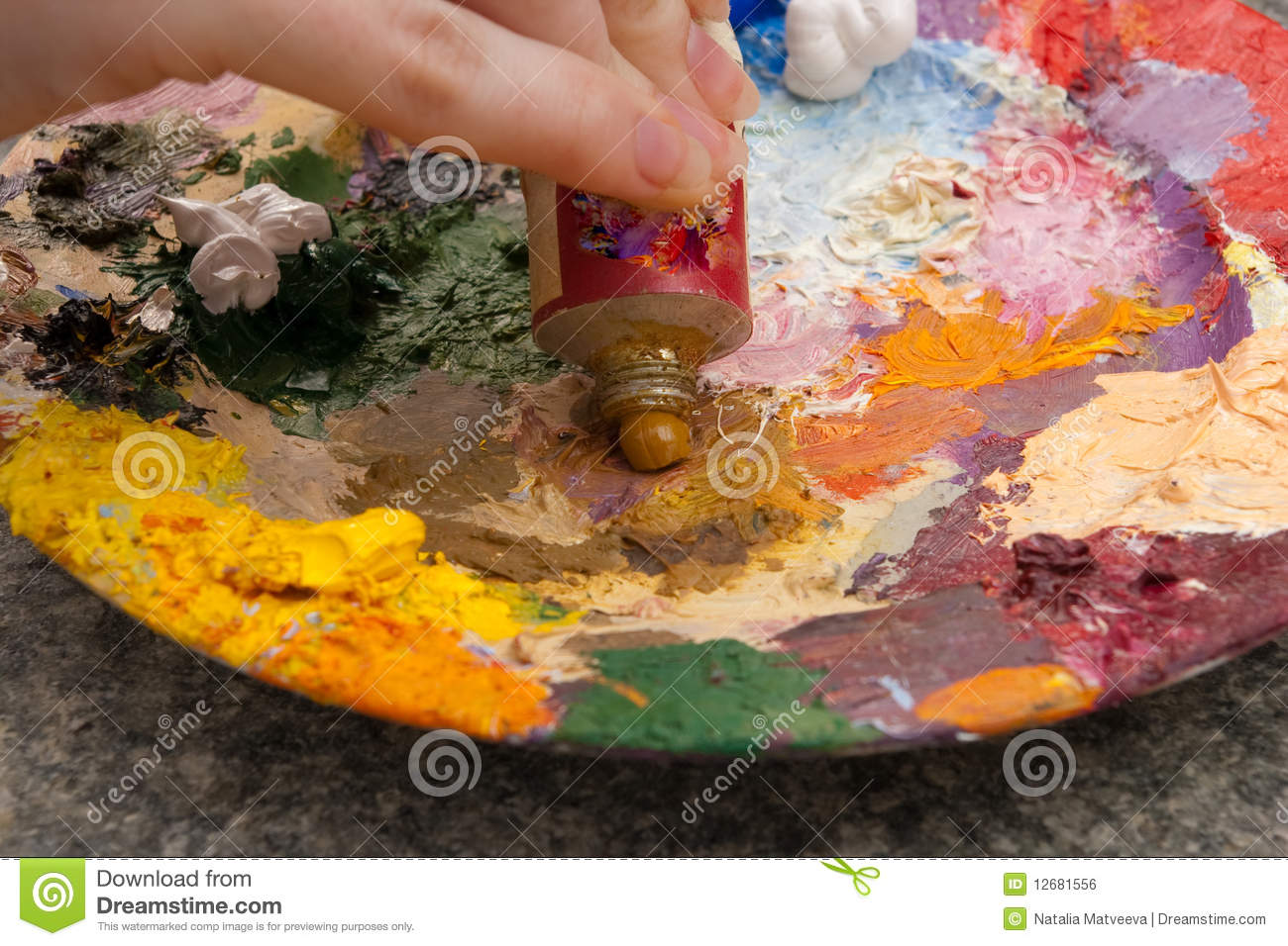 Hand squeezing yellow oilpaint on palette