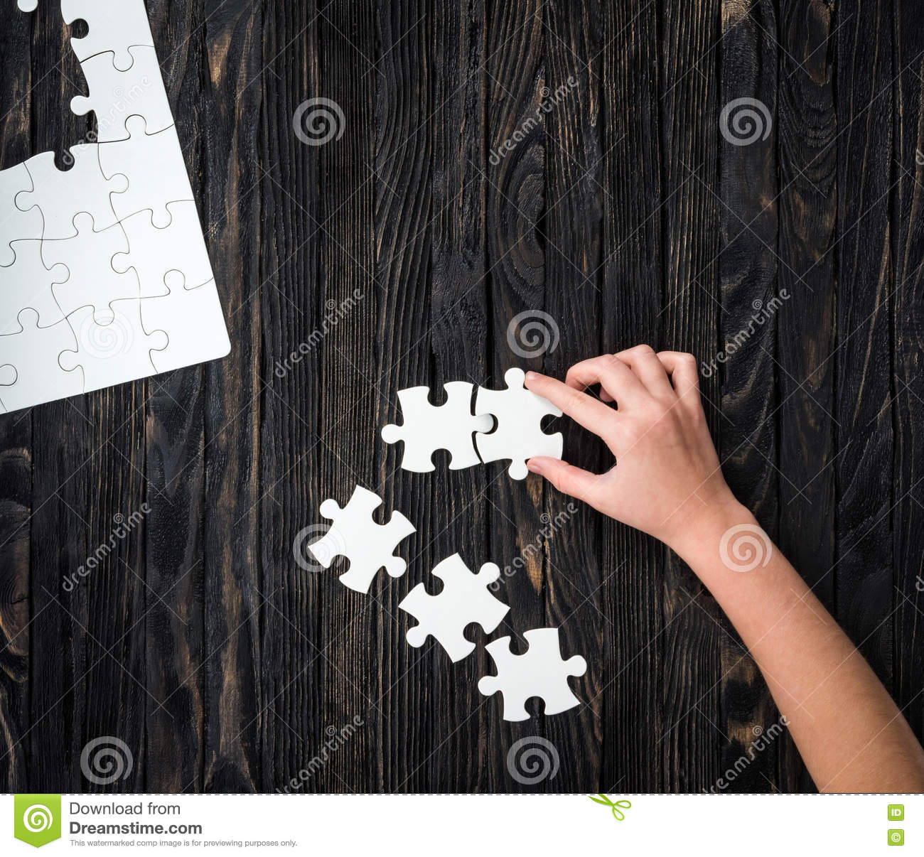 Hand starting to collect puzzle pieces