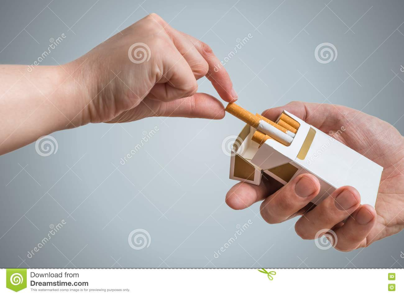 hand is taking cigarette from cigarette pack an accepting an offer hand is taking cigarette from cigarette pack an accepting an offer
