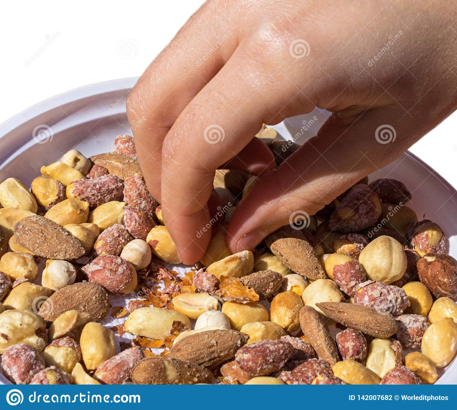 Hand taking some mixed snacks rice crackers, nuts and dried fruits