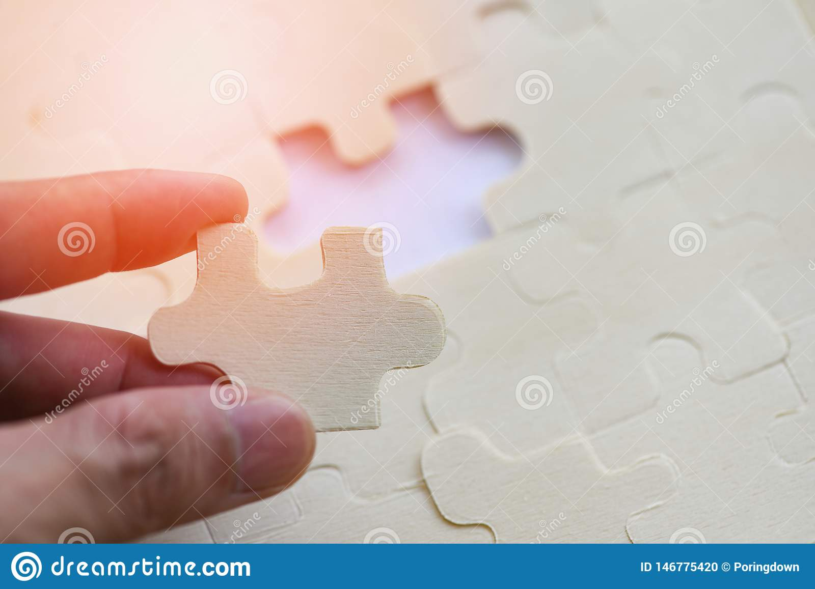 Hand trying to connect jigsaw puzzle on background jigsaw piece connecting