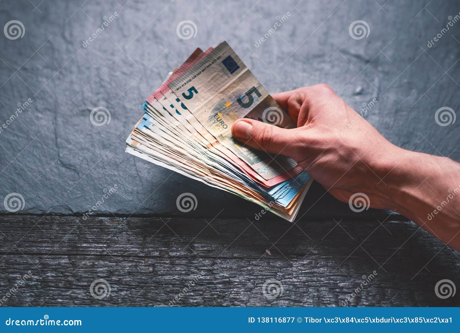 Handtrzyma pieniądze młody człowiek Banknoty na kamiennym tle Euro pieniędzy banknoty różna wartość