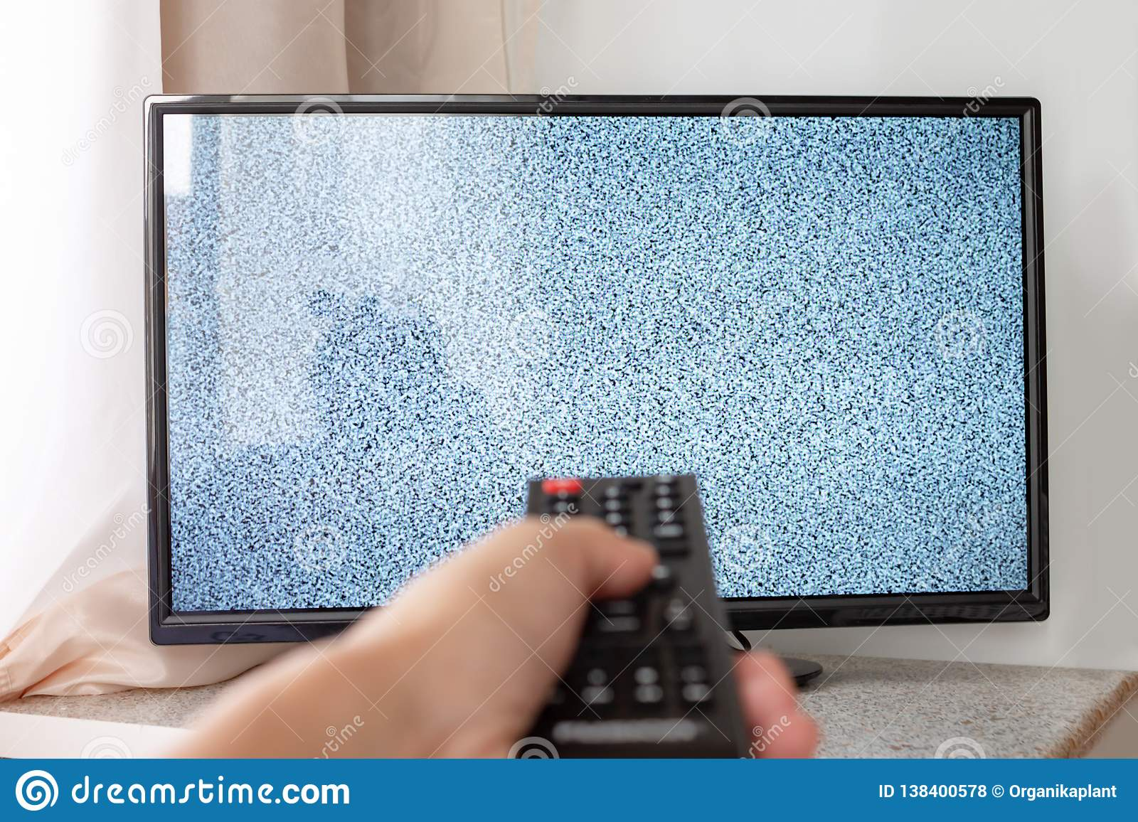 Hand with TV remote control in front of the screen with white noise on it - tuning the television channels and connecting problems